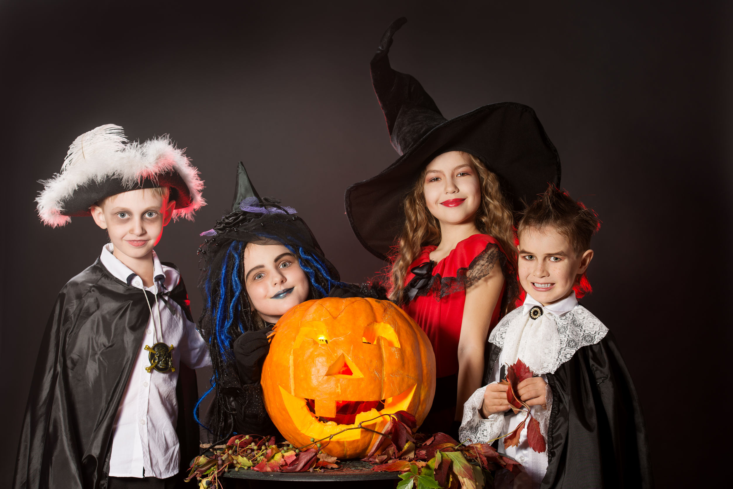 Niños alegres en disfraces de Halloween posando con calabaza