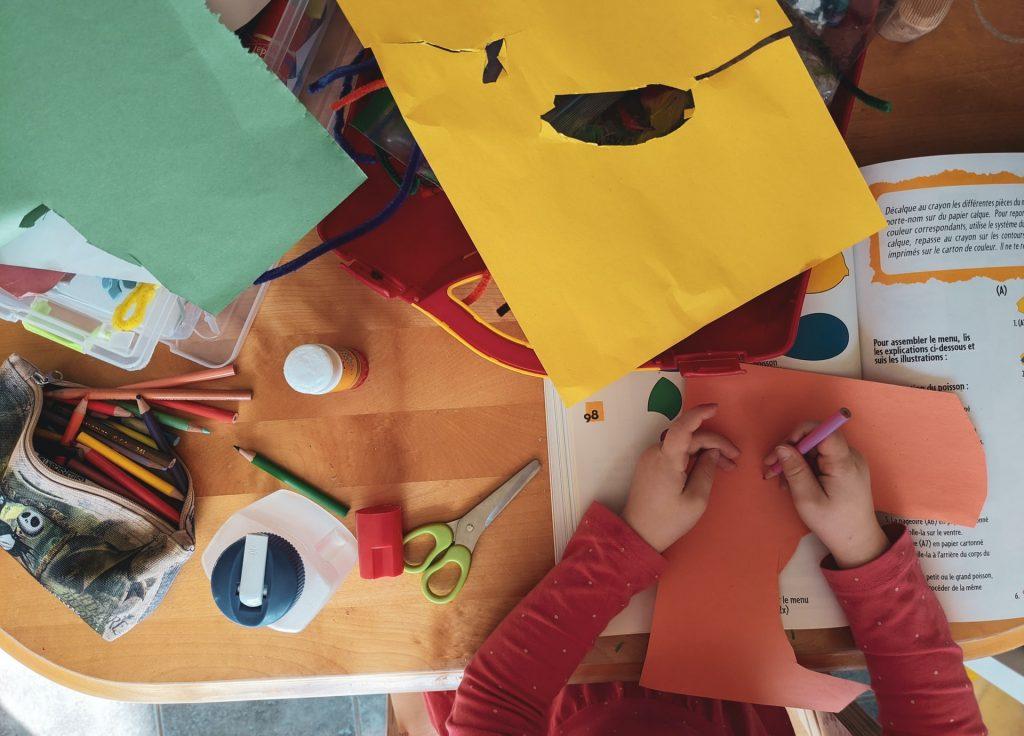 Niño utilizando lapices de colores en mesa con artículos para manualidades