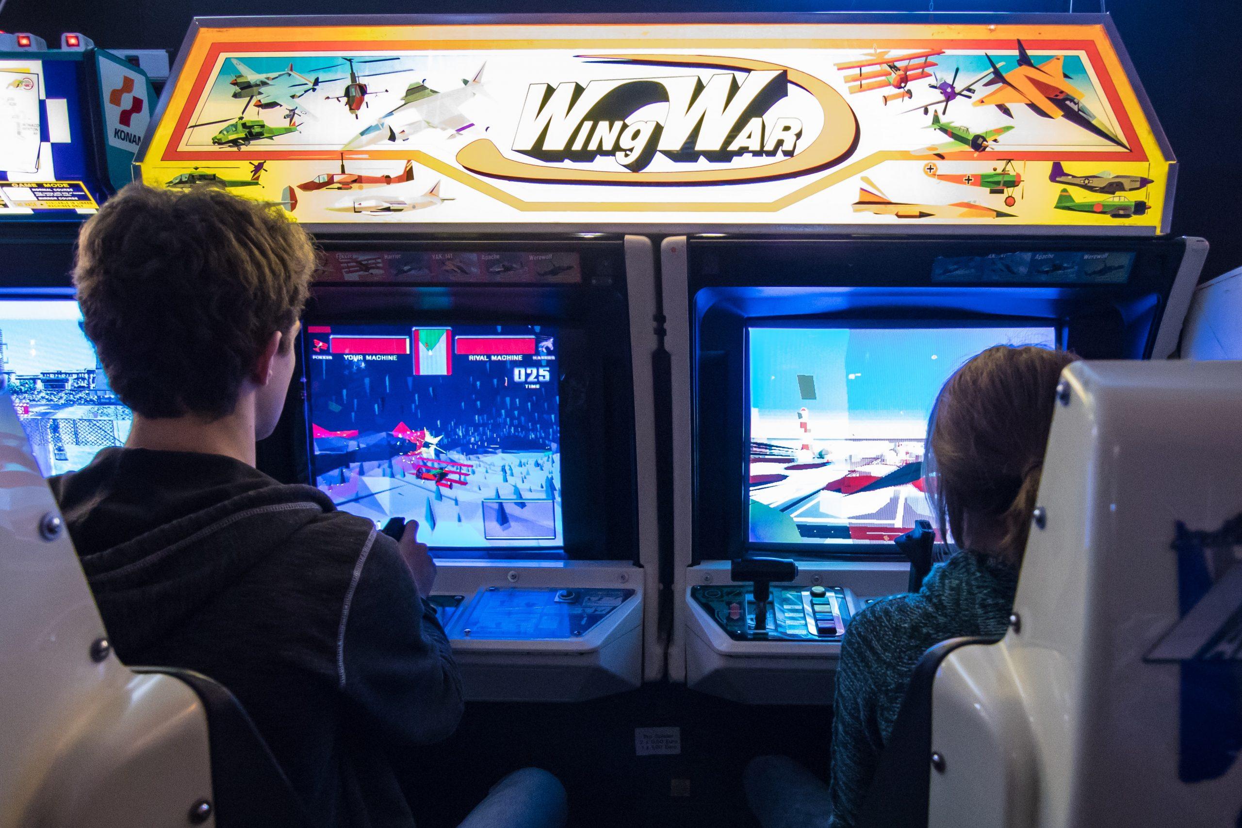 Dos niños jugando en maquinas arcade