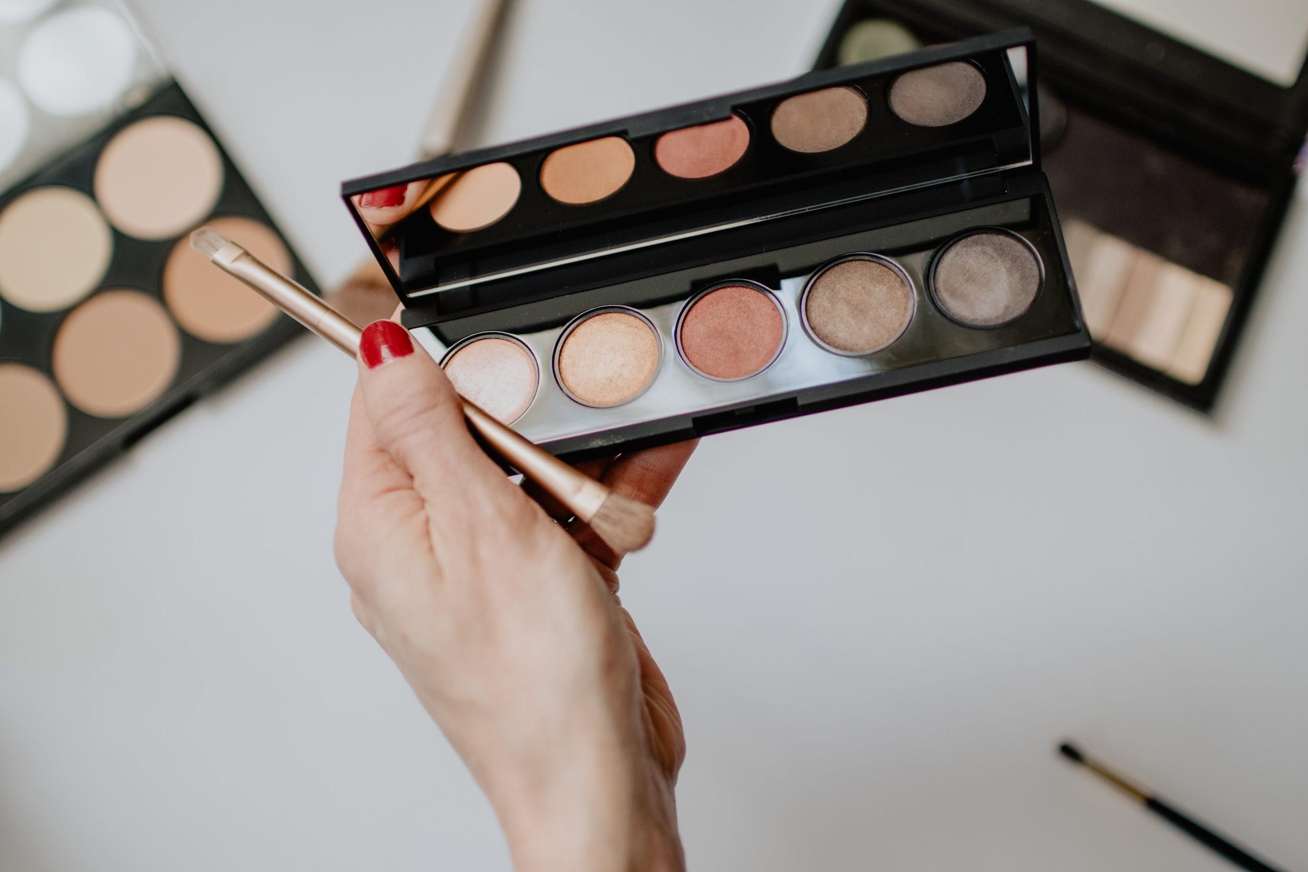 Mano de mujer sosteniendo paleta de maquillaje