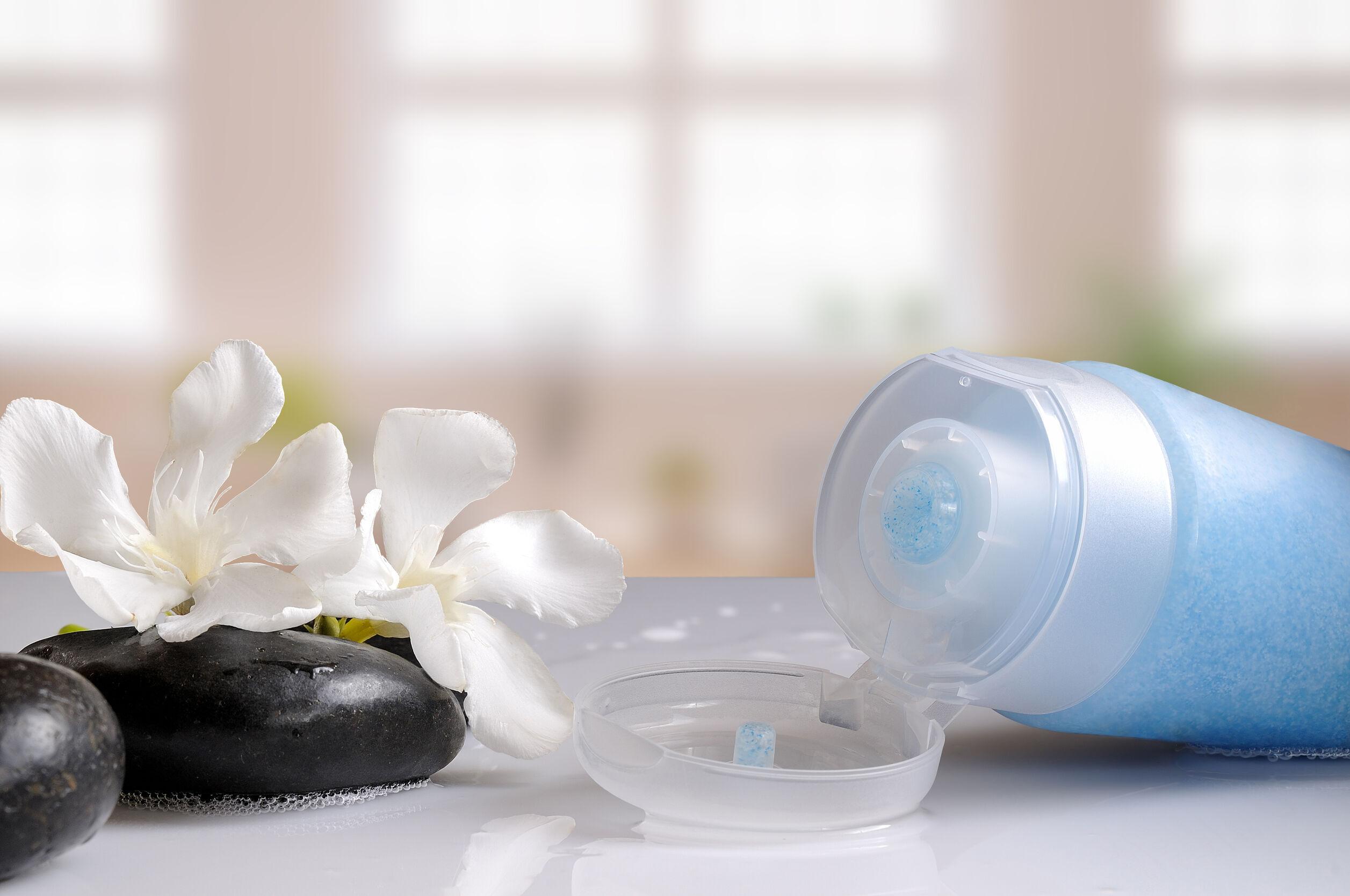 Gel exfoliante azul sobre una mesa de vidrio blanco en un baño