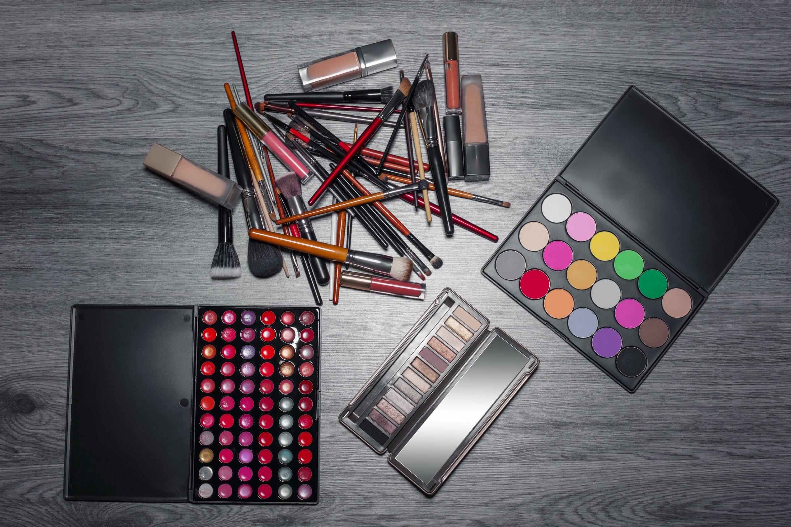 Varios itencilios de maquillajes en mesa gris