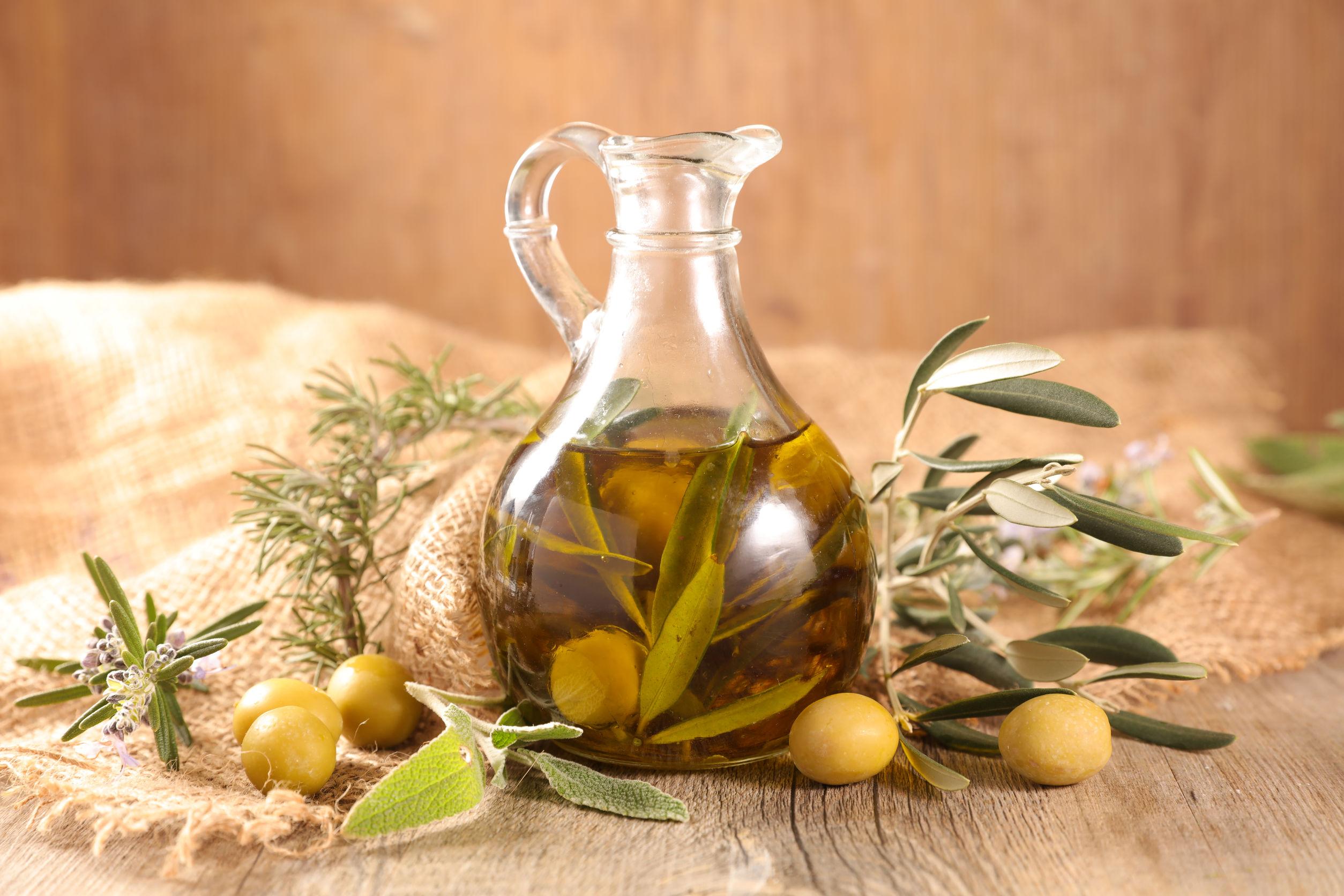 Jarra de aceite de olivo con hojas en su interior