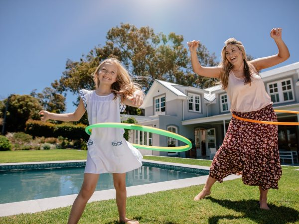 Happy mother and daughter twirling hula hoops. Beautiful young woman and little girl playing with hula hoop in their backyard.