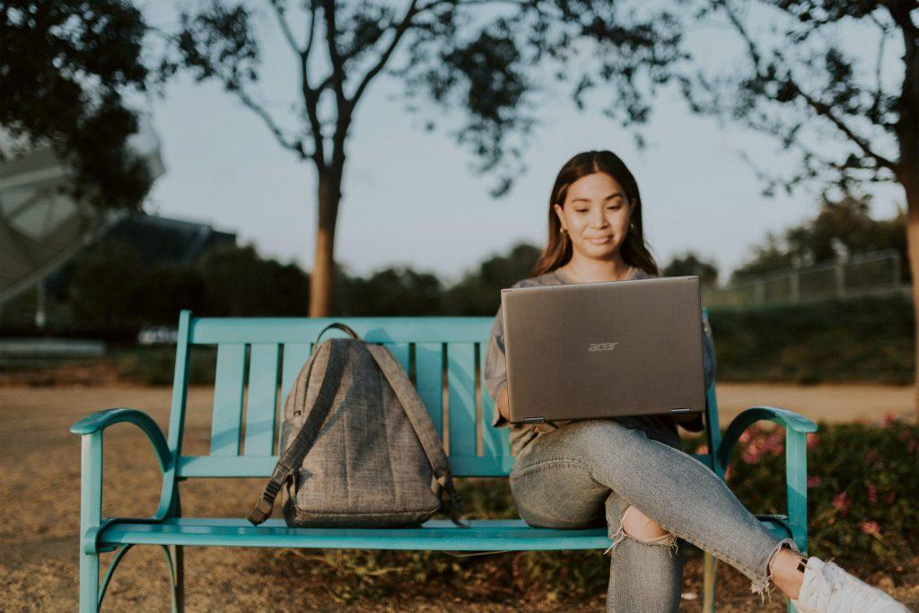chica en parque con ordenador