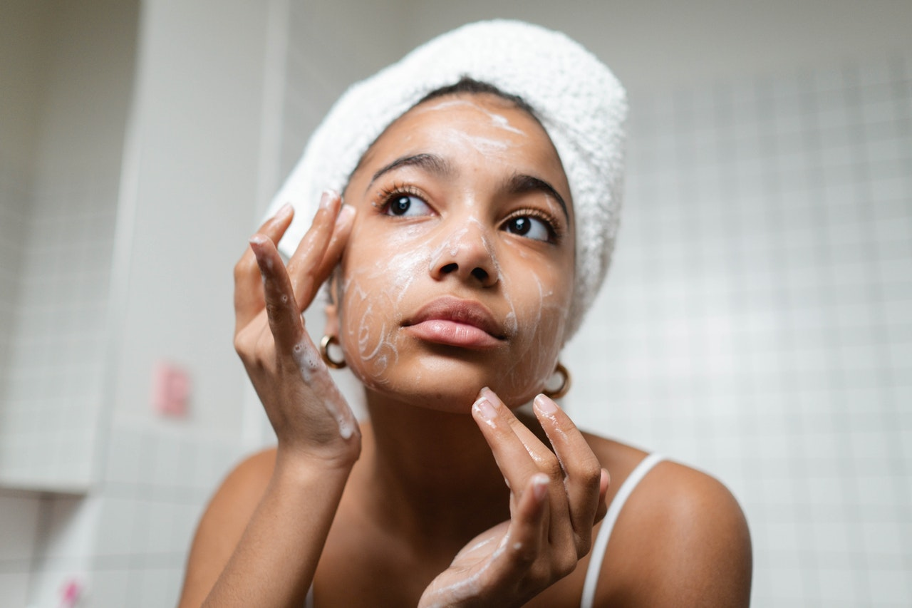Mujer aplicandose crema en el rostro