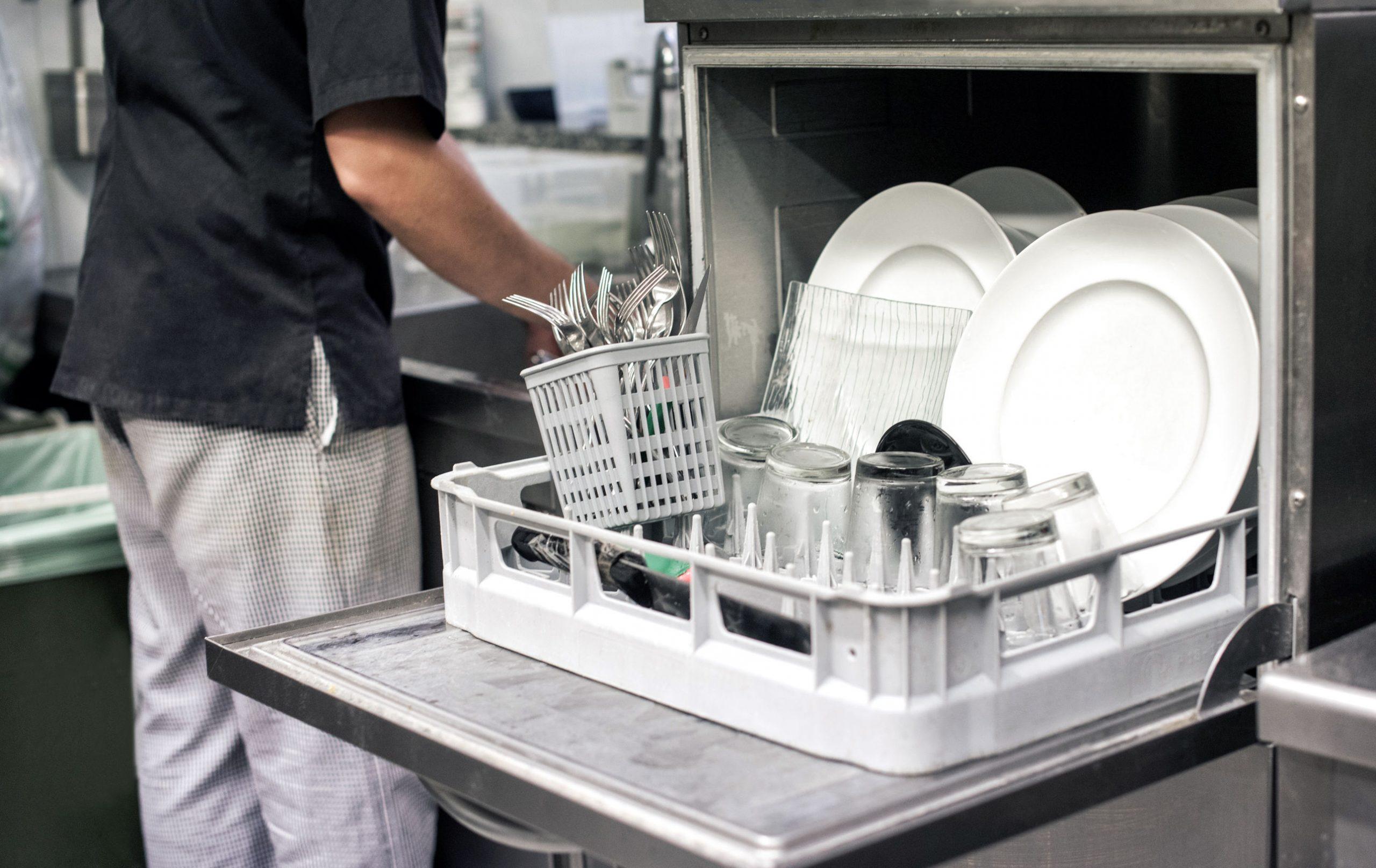 Mano de cocina con un lavavajillas abierto lleno de platos blancos limpios
