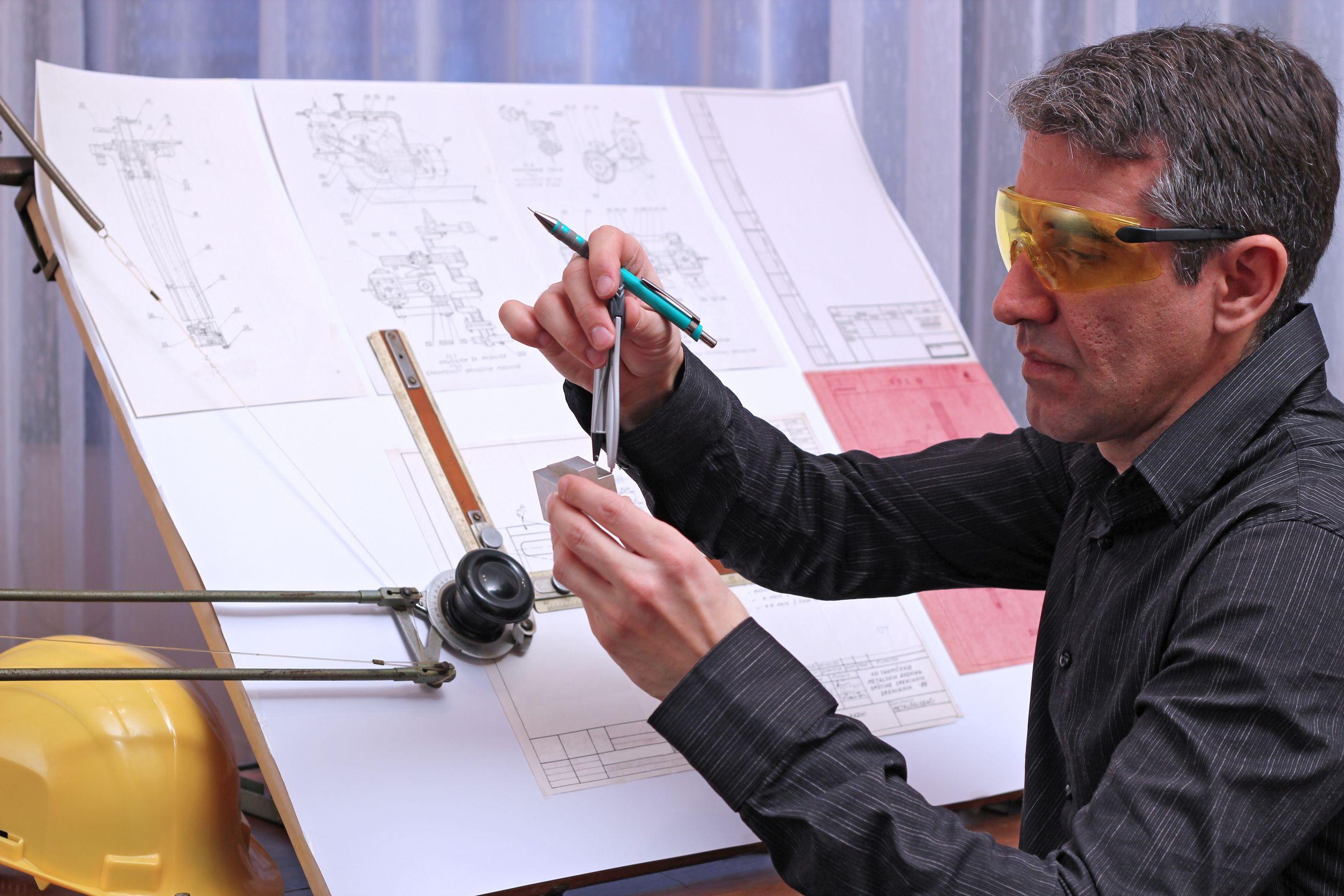 Medición de las dimensiones del modelo de metal con una pinza divisor y mesa de dibujo