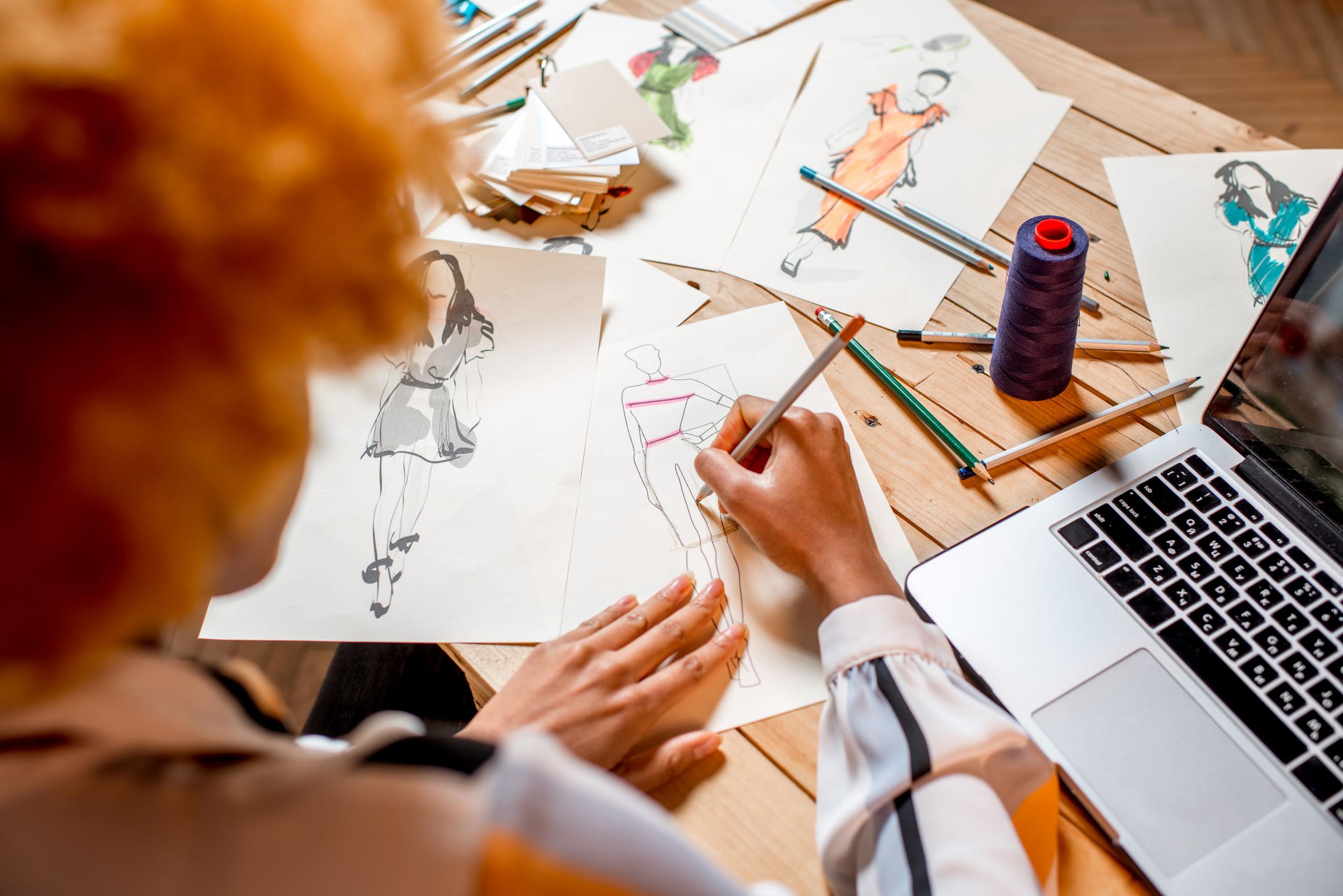 Diseñador de moda dibujando diseños de ropa en la mesa con un portátil y herramientas de confección
