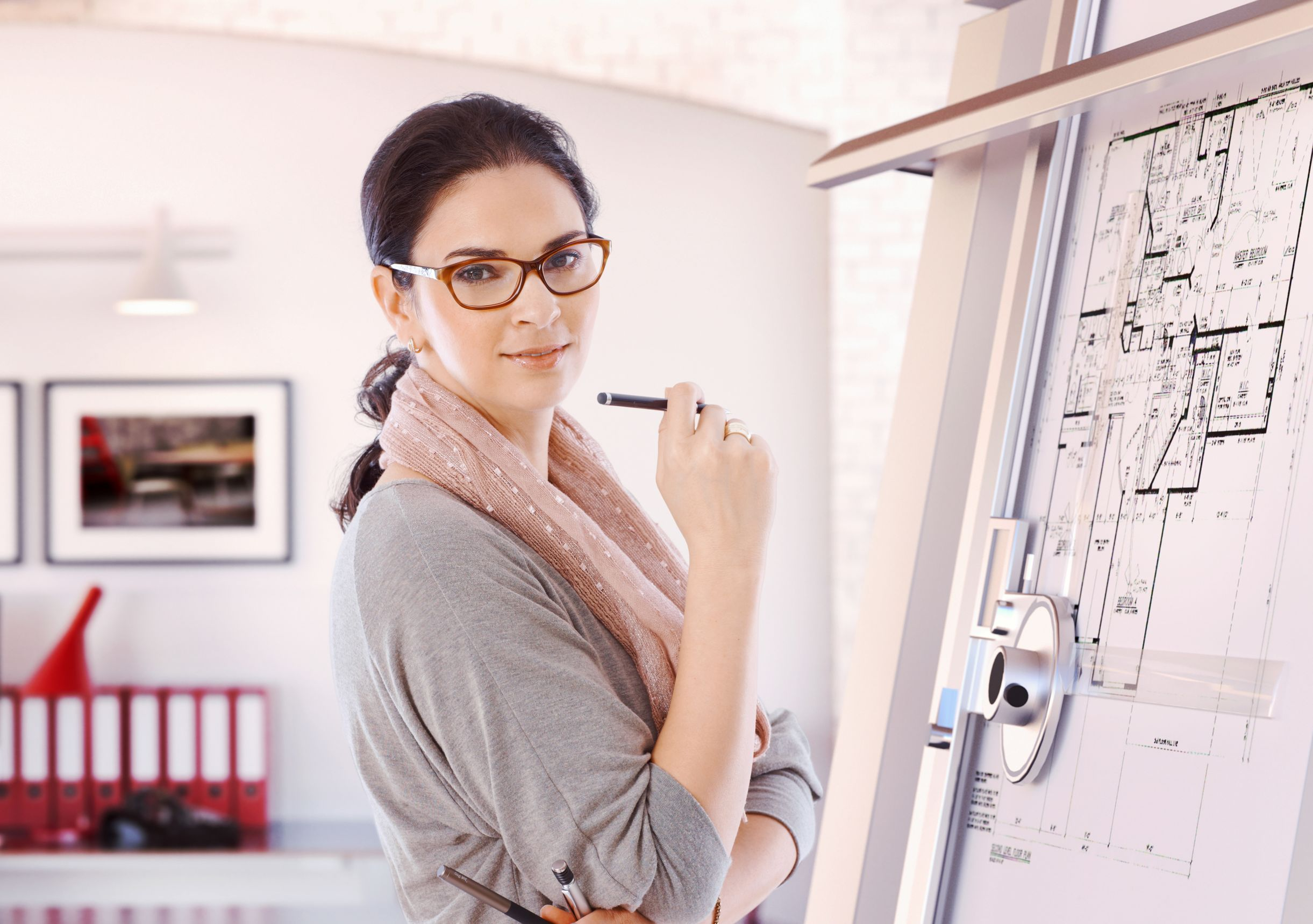 Arquitecta frente al tablero de dibujo con lápiz en la mano