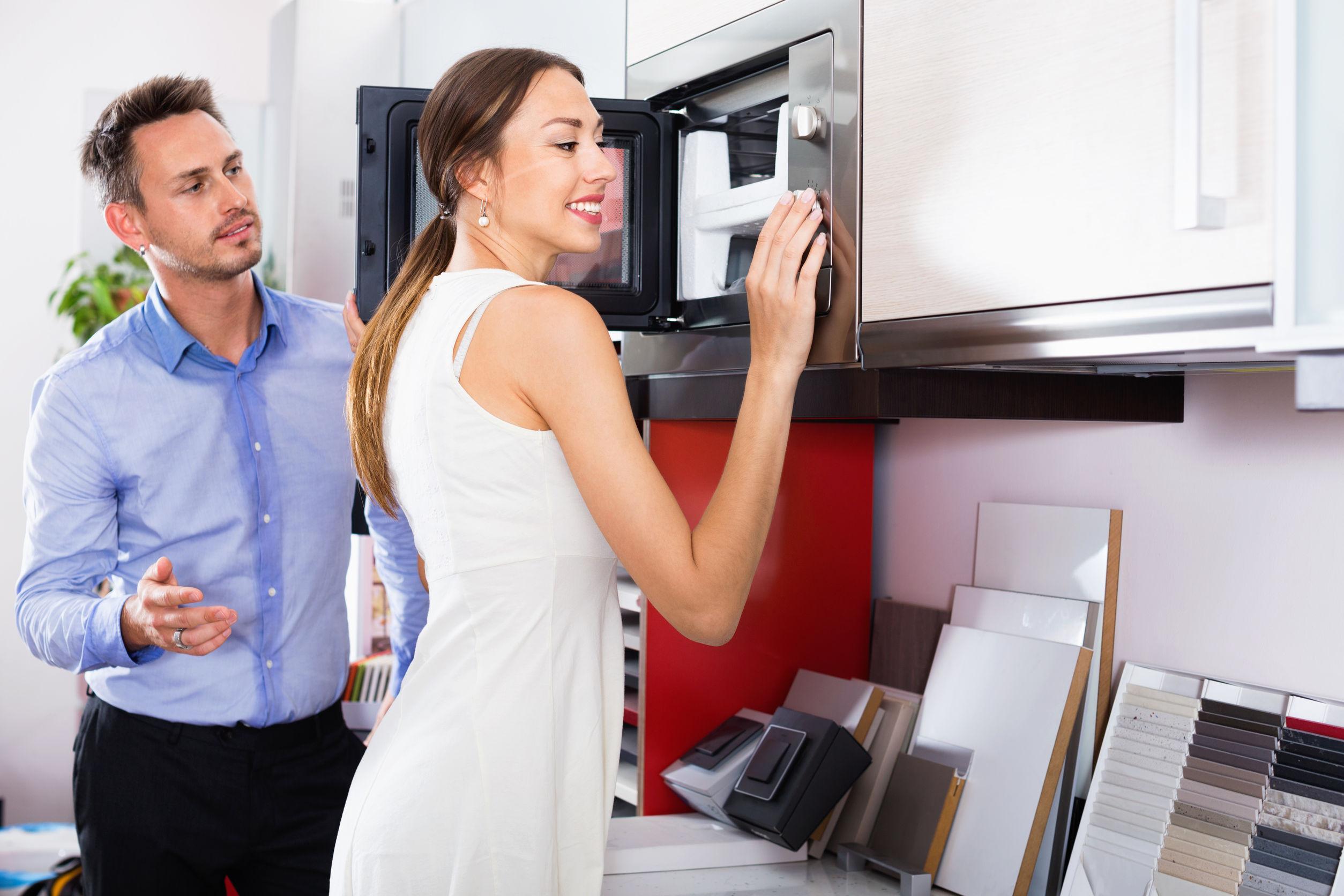 Joven pareja alegre feliz eligiendo microondas en la sección de electrodomésticos en la tienda de muebles