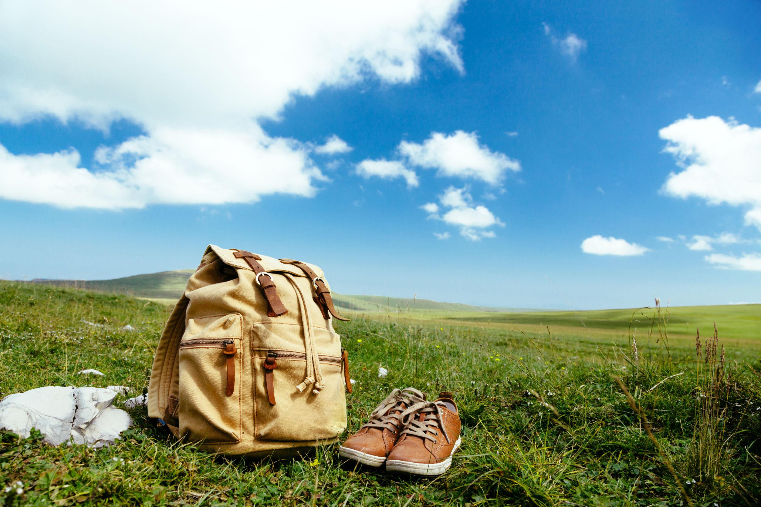 Mochila de viaje y los zapatos en la hierba verde en el campo de la primavera