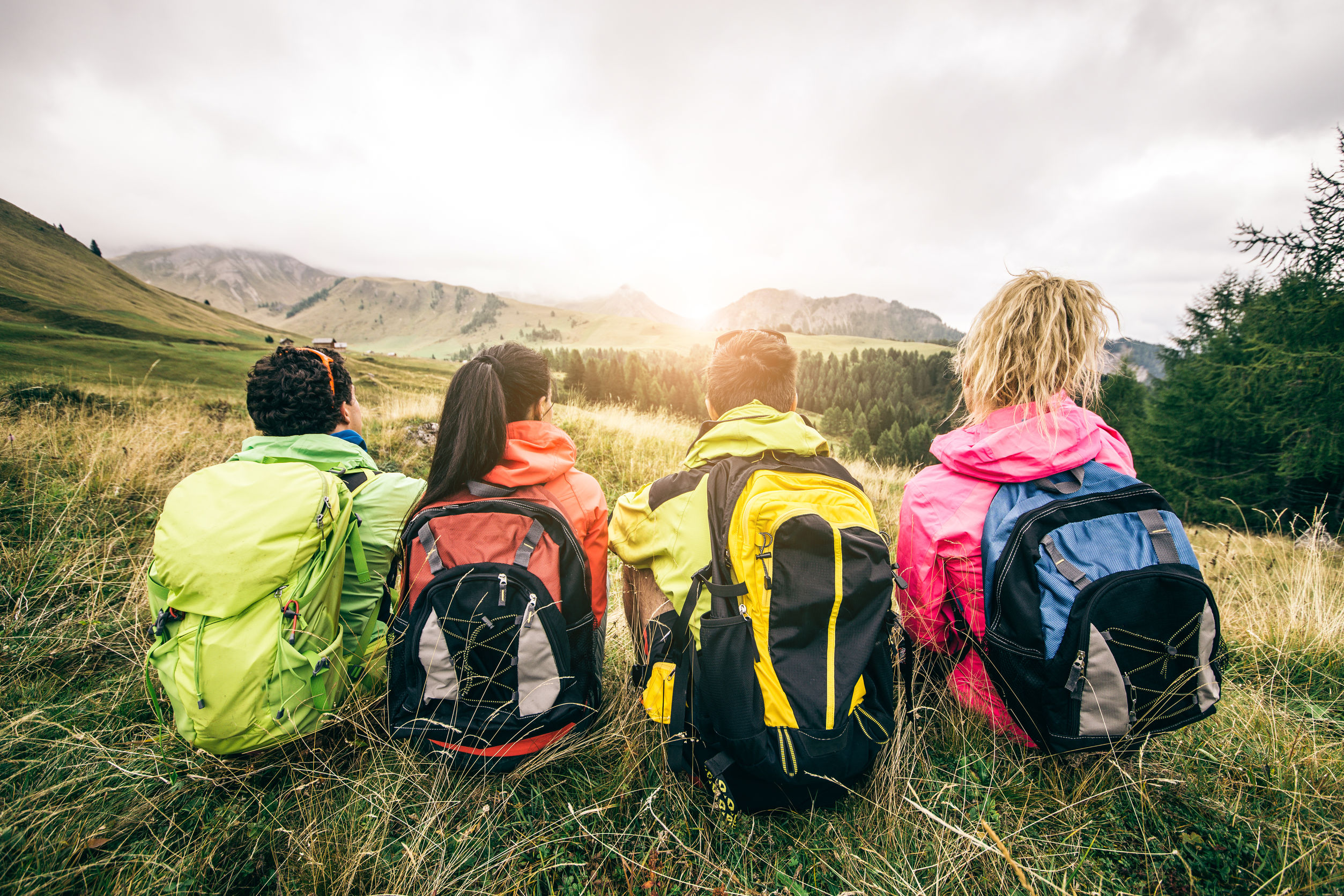 Varas mujeres de espaldas con mochilas de senderismo