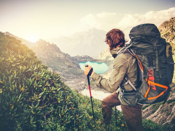 58406831 – man traveler with big backpack mountaineering travel lifestyle concept lake and mountains on background summer extreme vacations outdoor