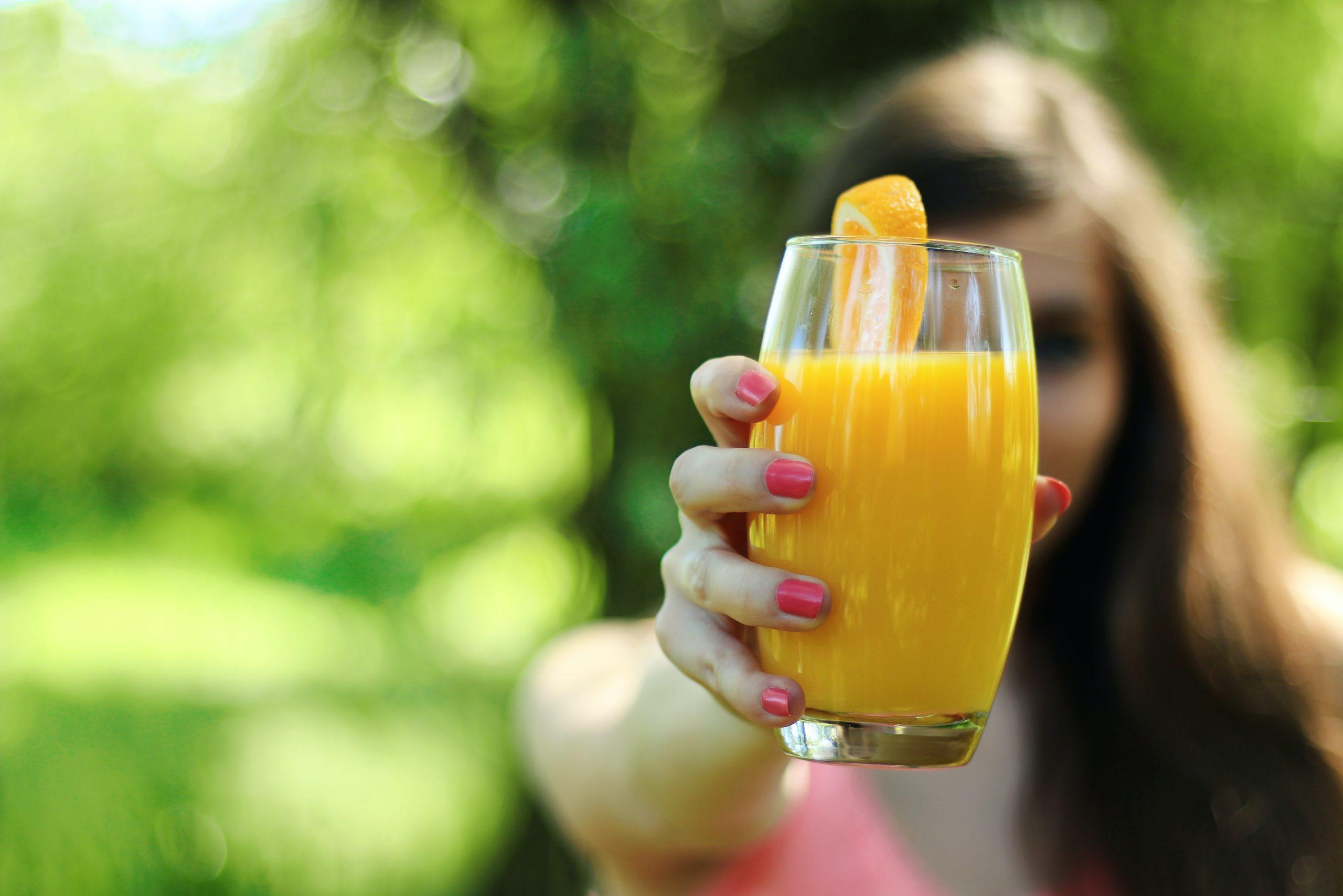 chica mostrando un zumo natural de naranja