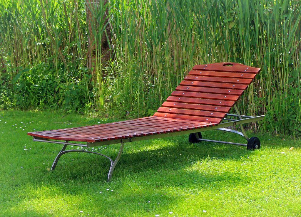 Tumbona de madera color rojo en el jardín