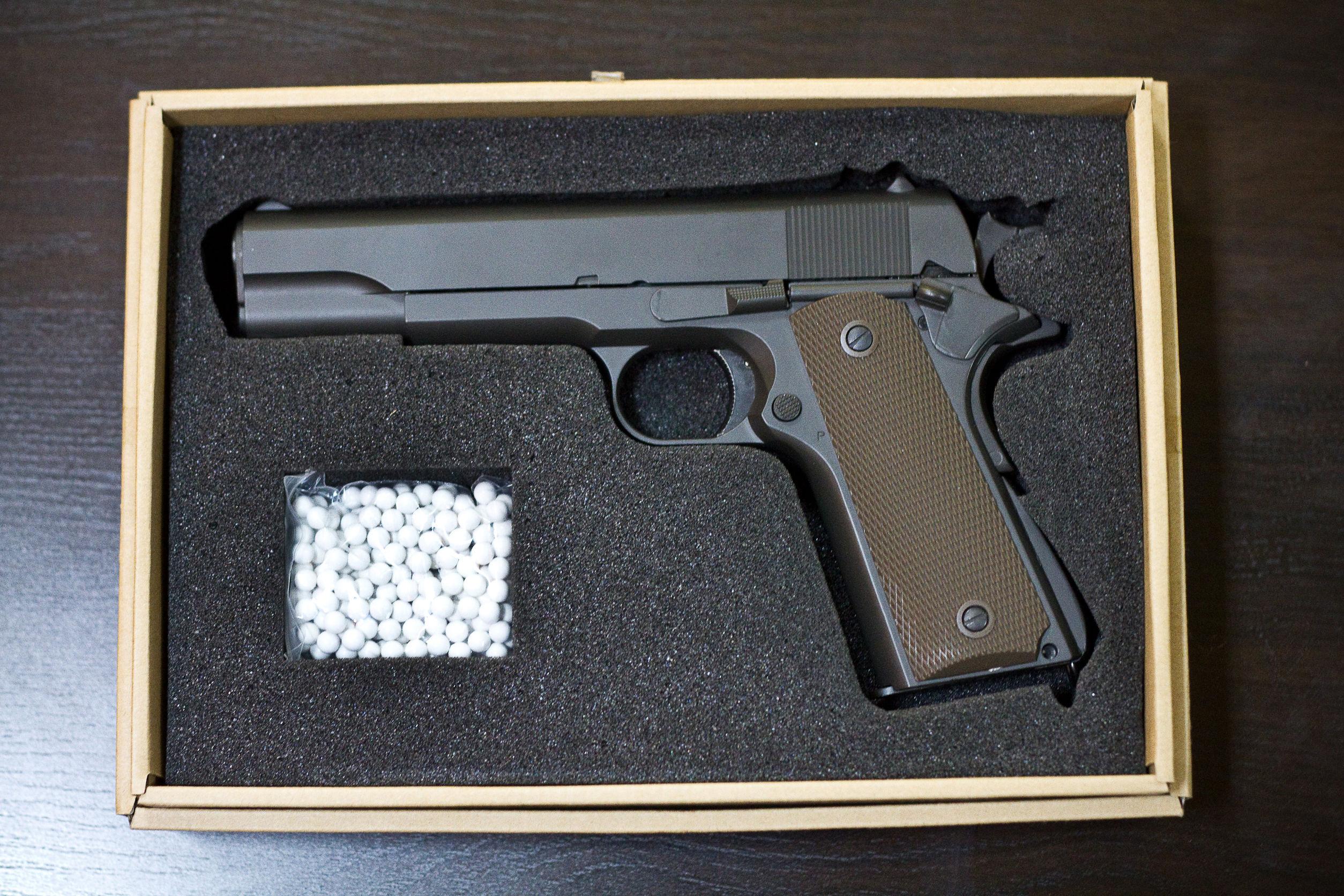 Pistola Strikeball con balas bb en una caja de cartón sobre un escritorio brillante