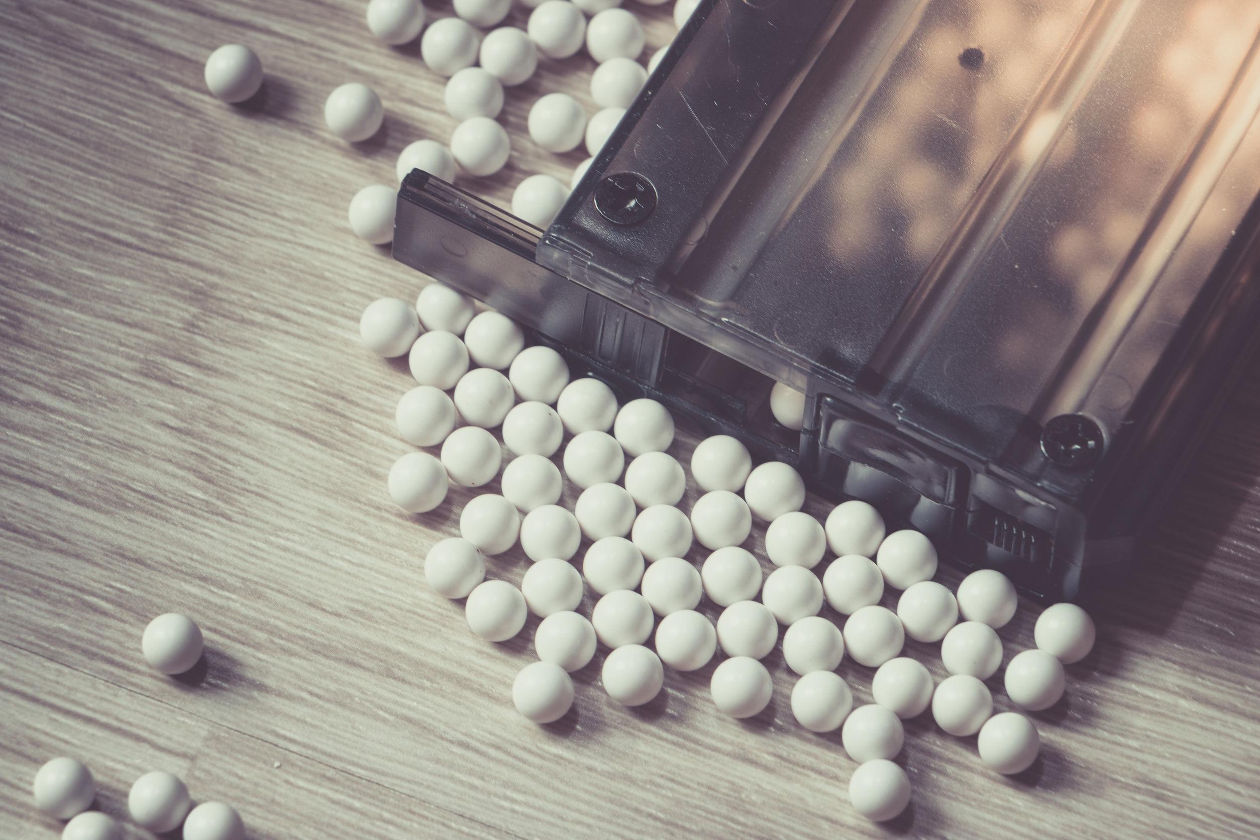 Munición con bolas metálicas BB y cargador sobre fondo de madera.