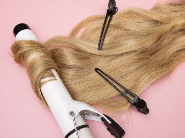 Curling blonde hair on a large diameter curling iron on a pink background. Curl care, hair styling, black clips. High quality photo