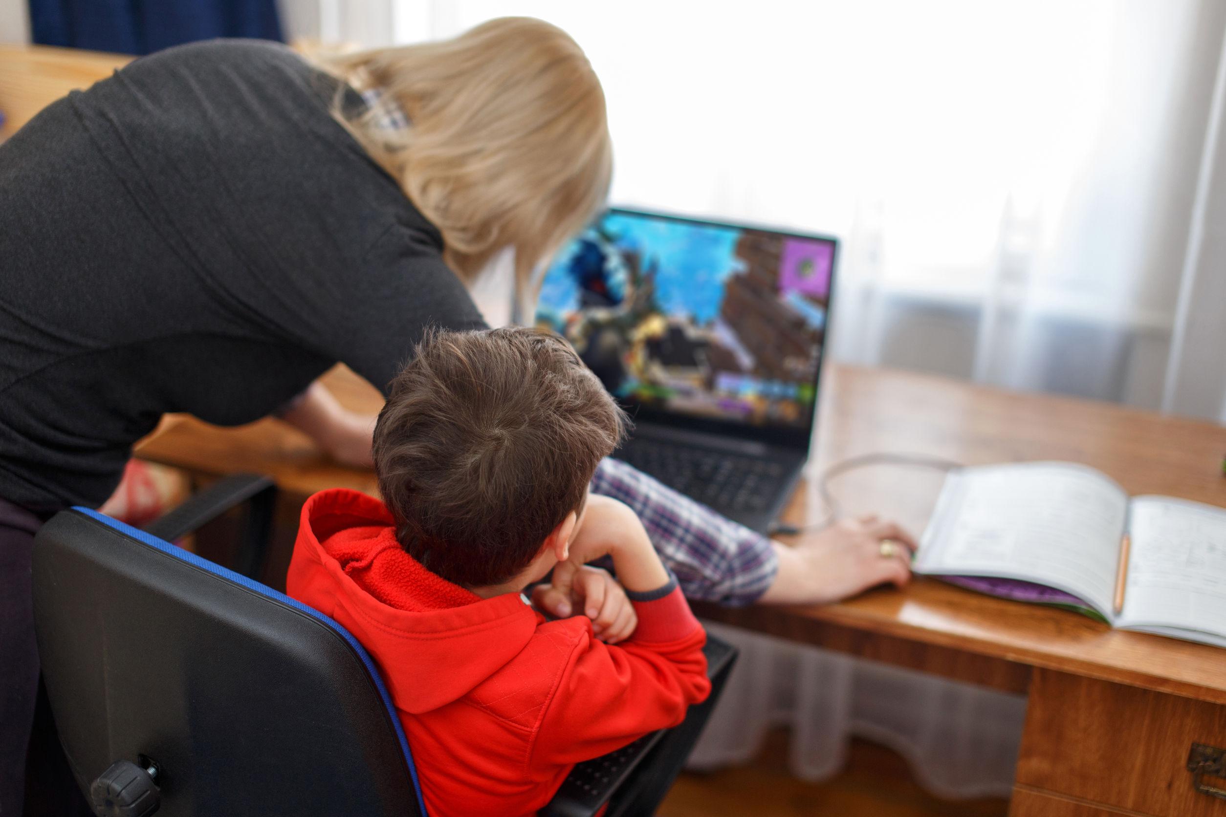 Madre supervisando hijo que juega en la computadora