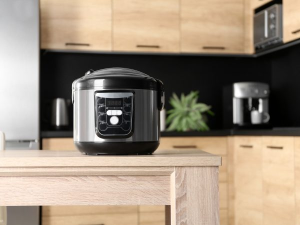 Modern multi cooker on table in kitchen, space for text