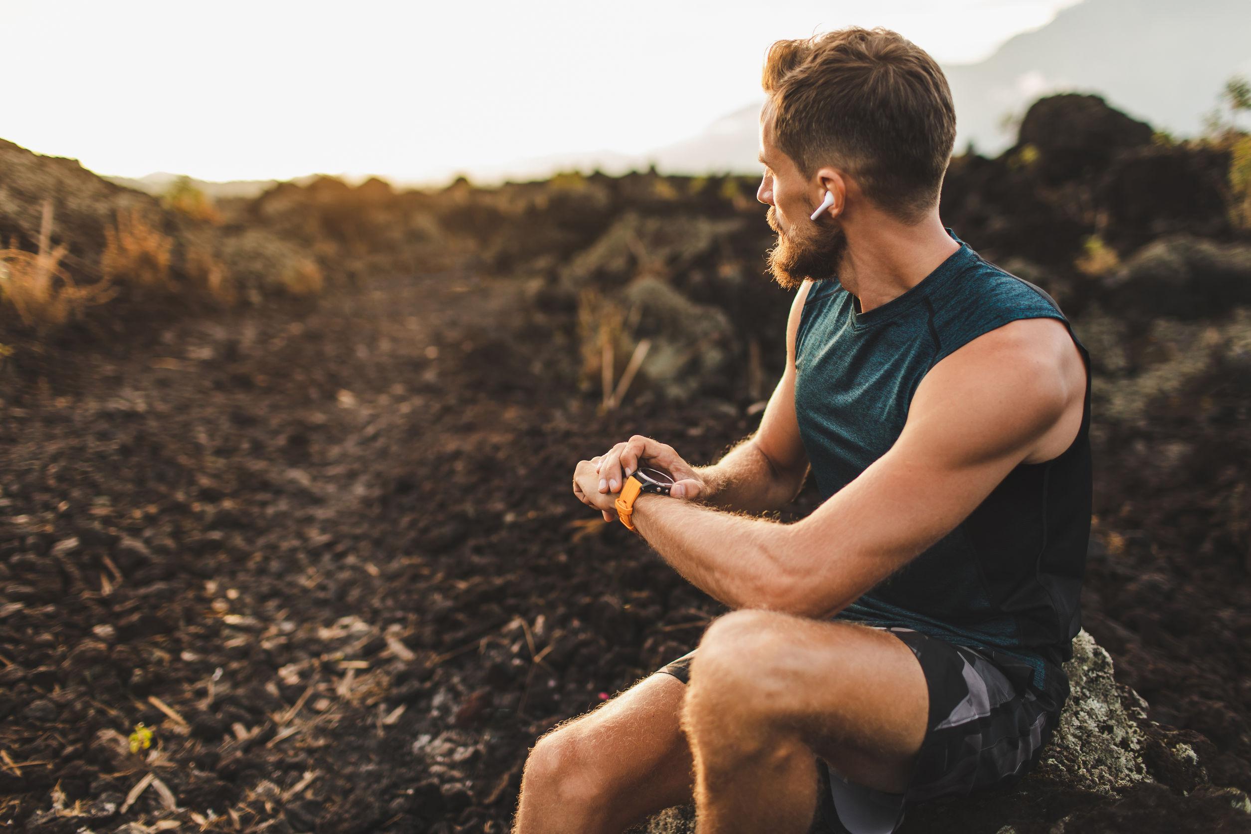 El corredor atlético comienza a entrenar en un rastreador de ejercicios o un reloj inteligente y mira hacia el horizonte