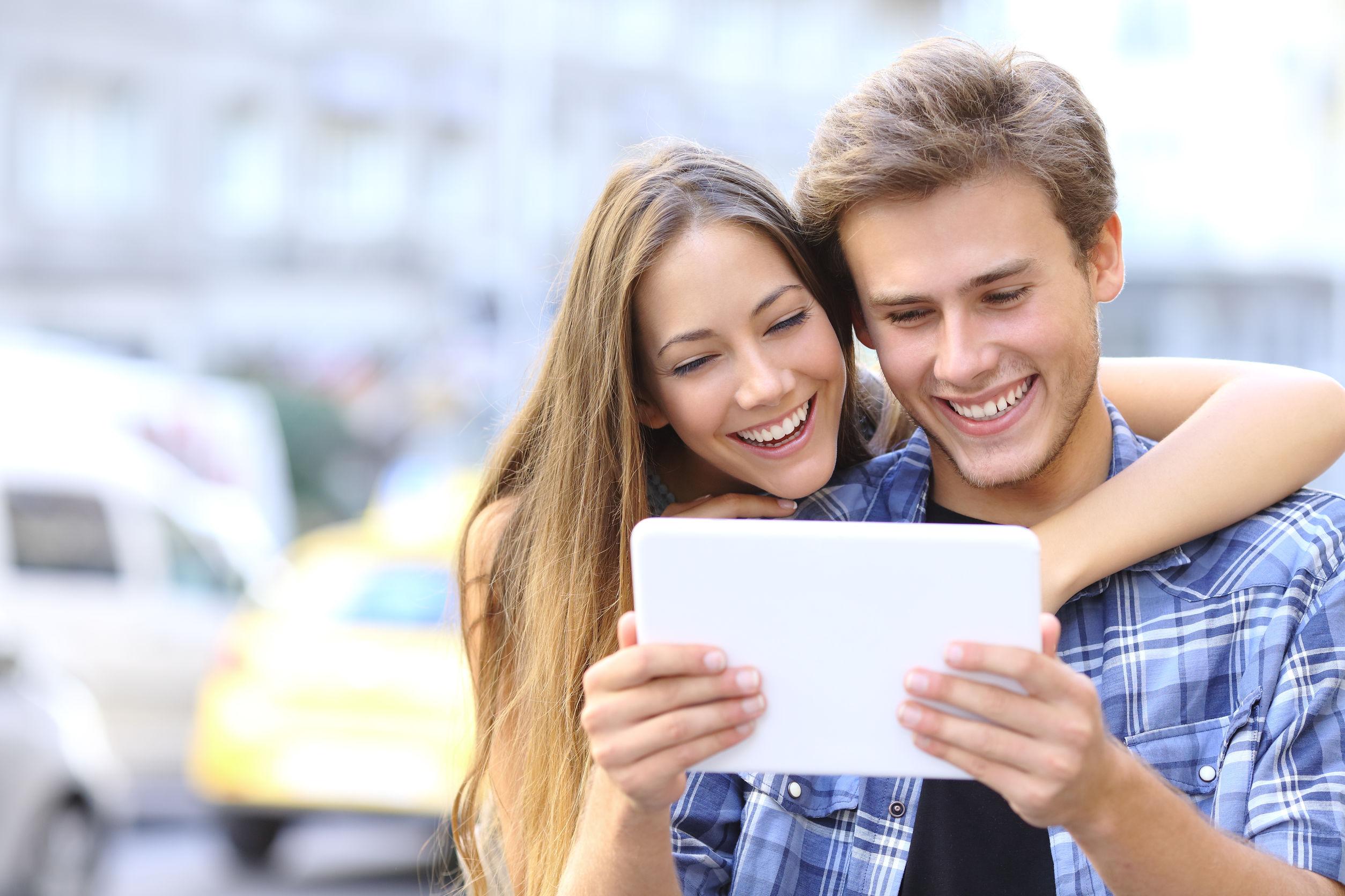 Pareja de jovenes sonrientes sosteniendo una tablet