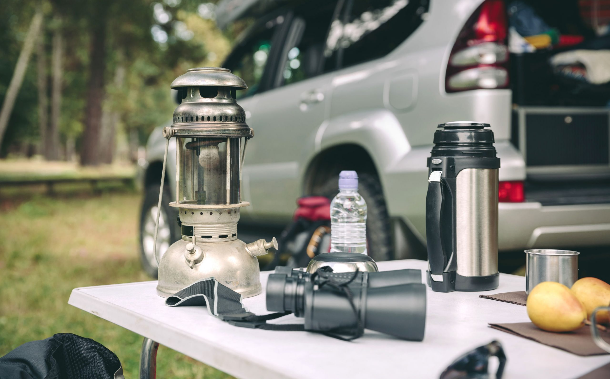 Lámpara de aceite, termo y binoculares sobre una mesa de camping en el bosque con un vehículo todoterreno en el fondo