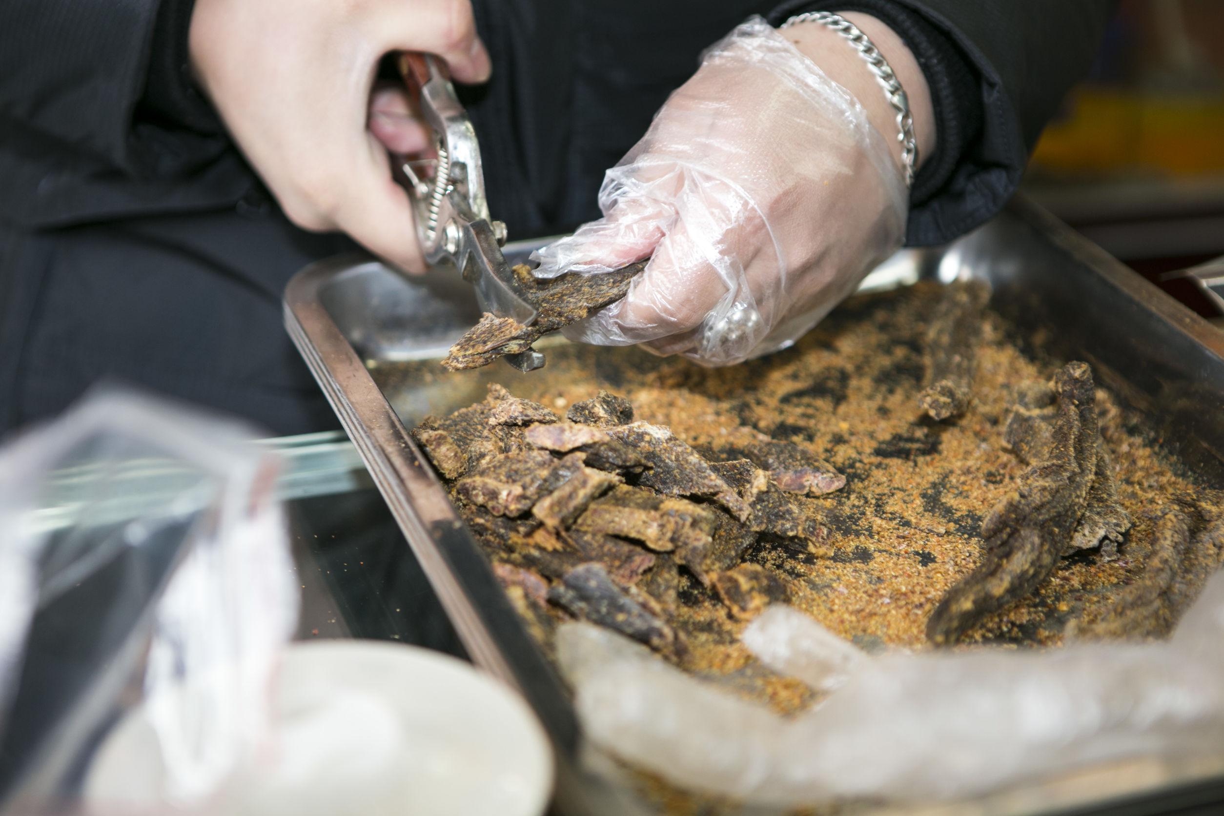 Cerca de la mano que sostiene las tijeras de podar cortando carne seca en bandeja de acero inoxidable