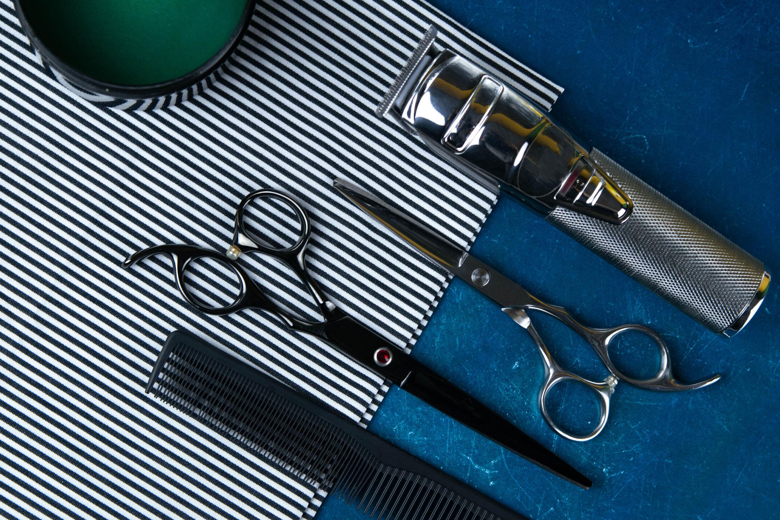 na máquina de corte de pelo con tijeras sobre una hermosa toalla a rayas que se encuentra sobre un fondo azul.