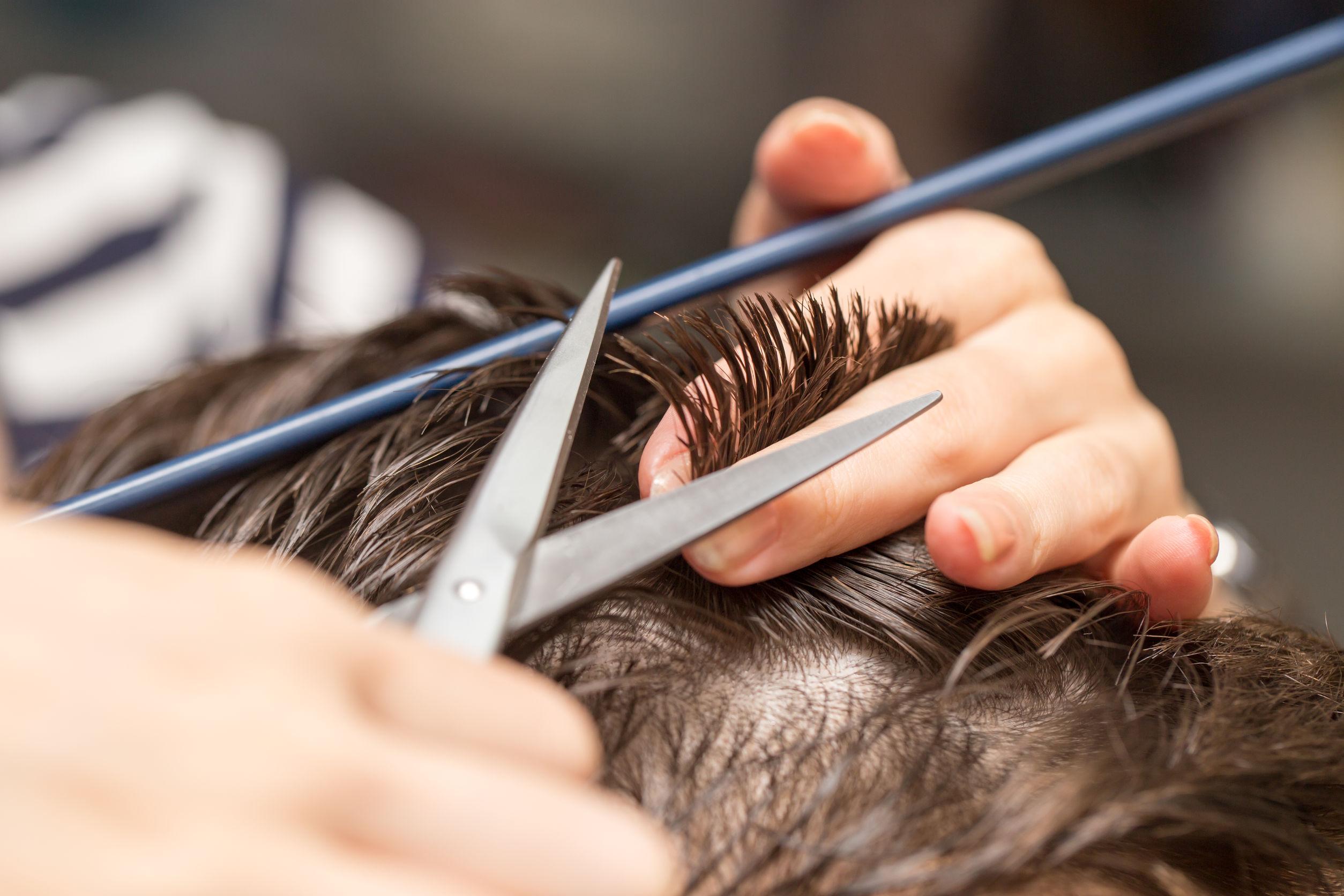 Persona cortando el cabello con tijeras a un hombre