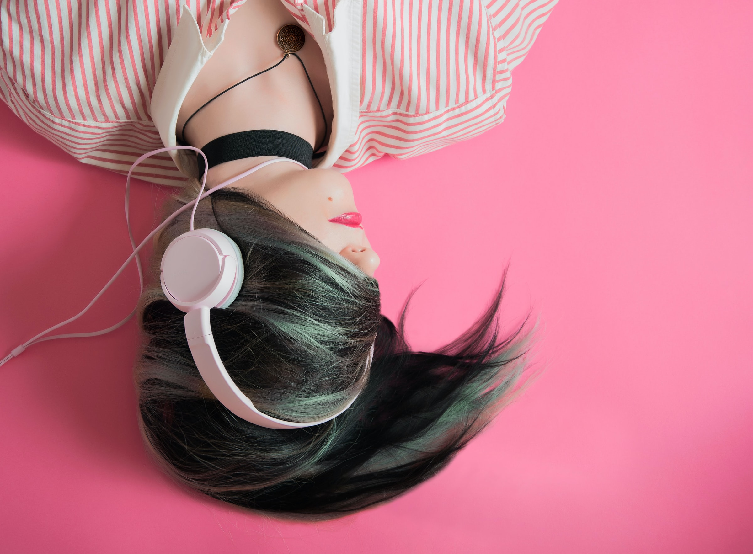 Chica utilizando auriculares de diadema sobre fondo rosa