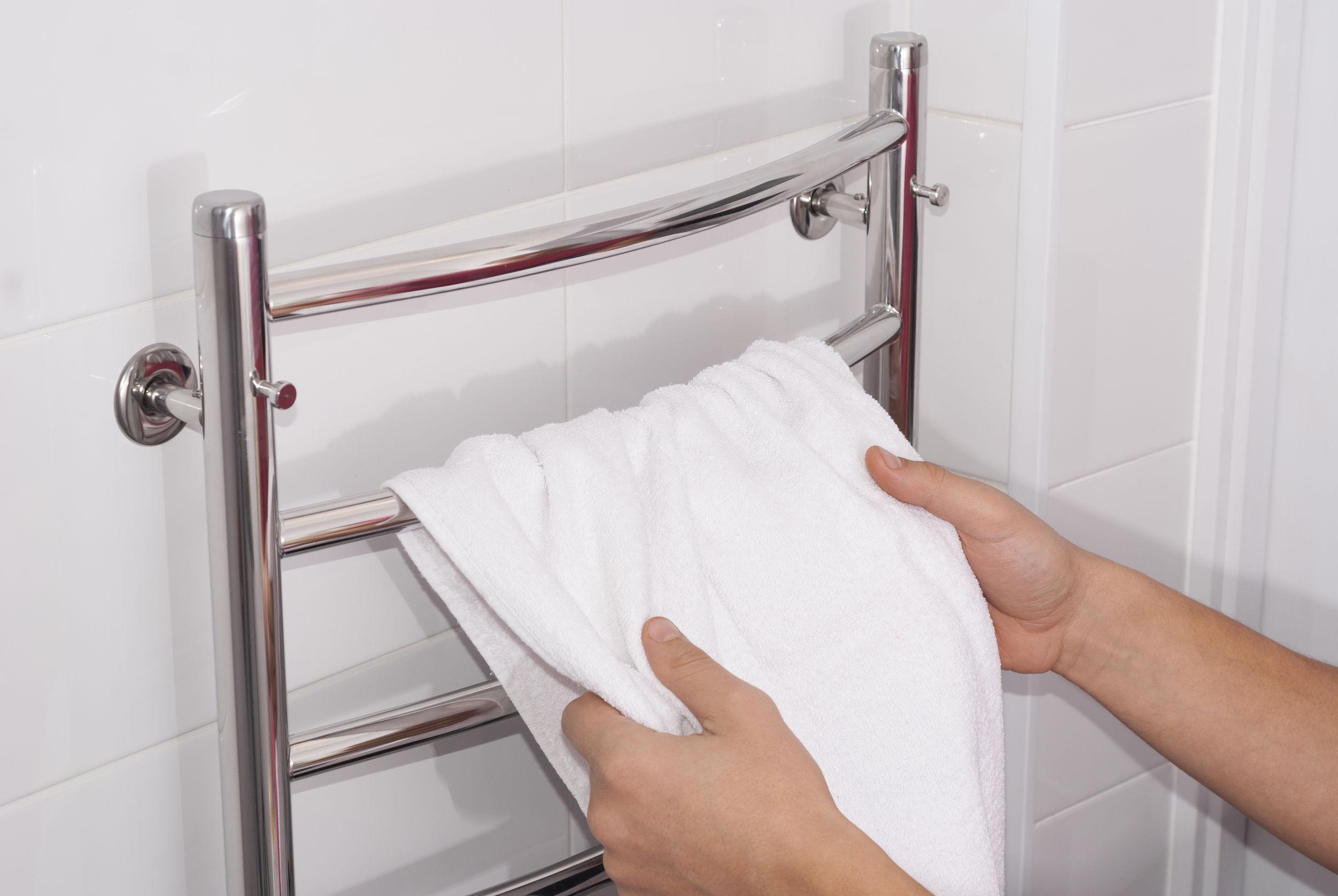 Hombre cuelga una toalla en la secadora en el baño