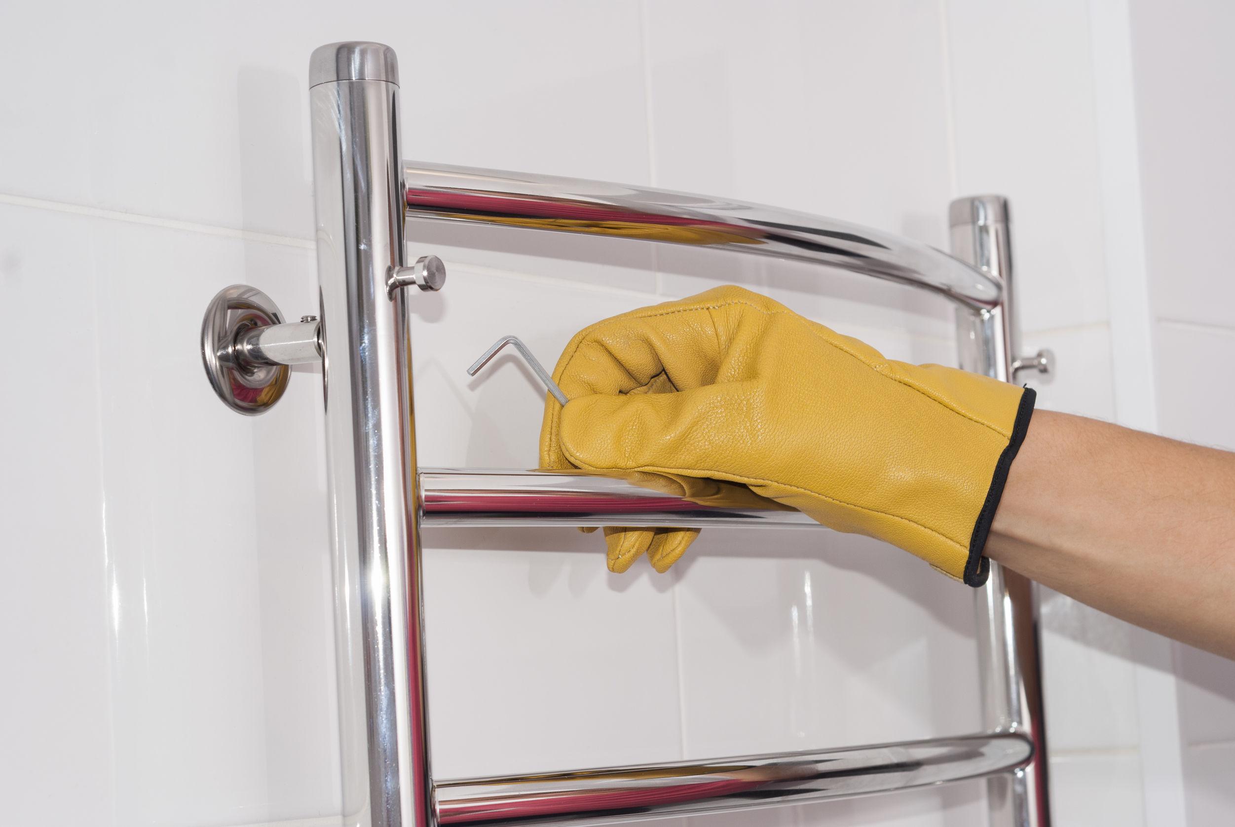 El hombre instala un toallero eléctrico con calefacción en el baño