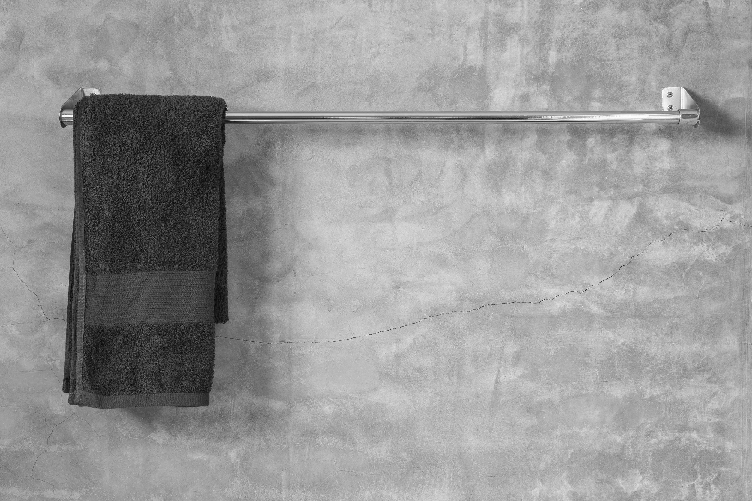 Toallero de acero inoxidable en la pared de cemento gris con la toalla marrón en el baño