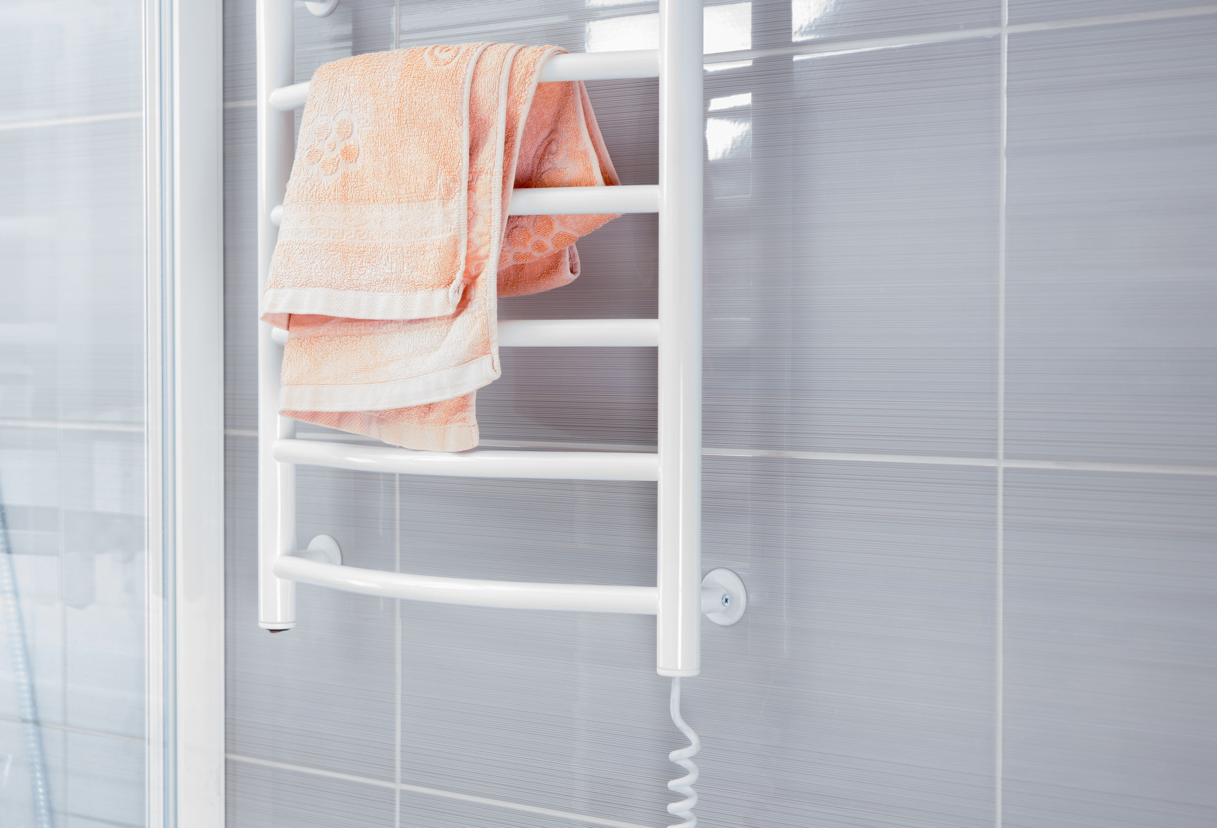 Baño vacío con la pared de la ducha gris de color blanco detrás de la rejilla para calentar el metal con una toalla de color rosa en la parte superior plegada