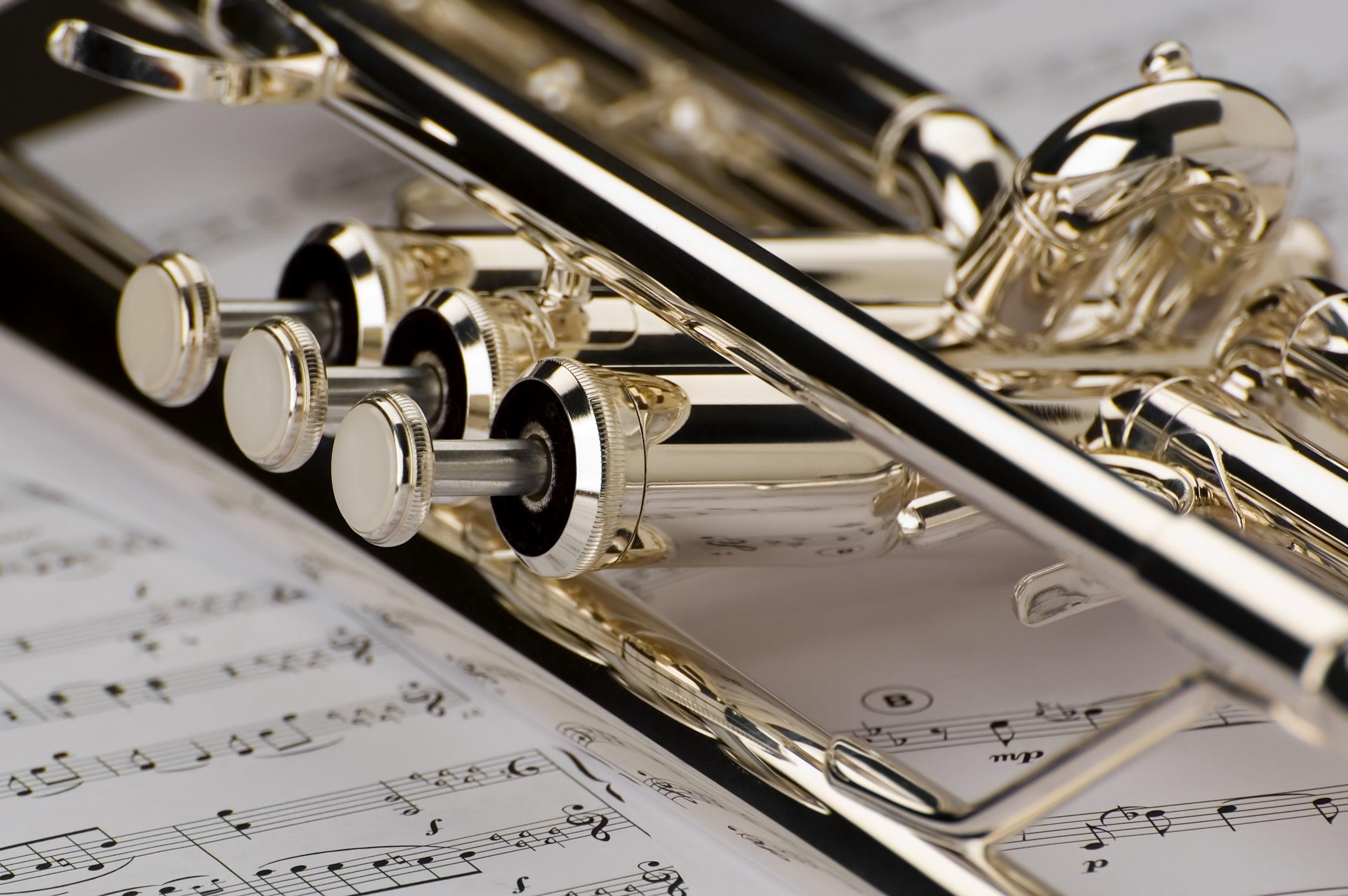 Trompeta en notas musicales como fondo de cerca