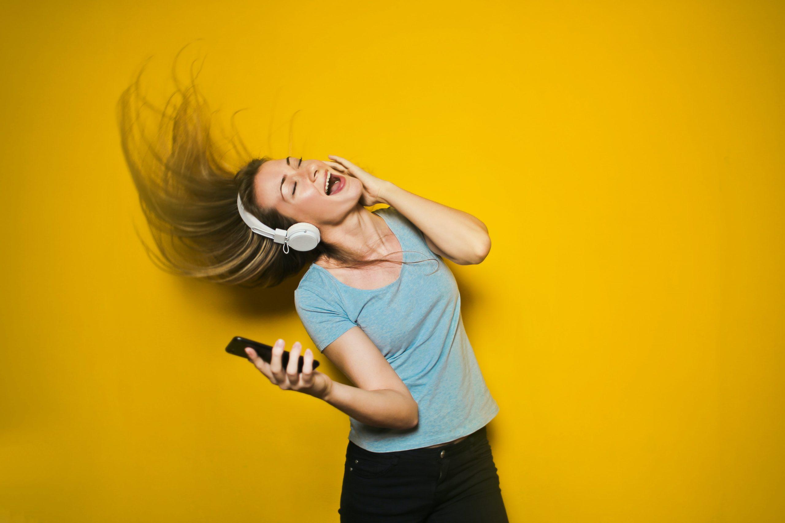 Mujer joven escuchando musica con auriculares de diadema sobre fondo naranja