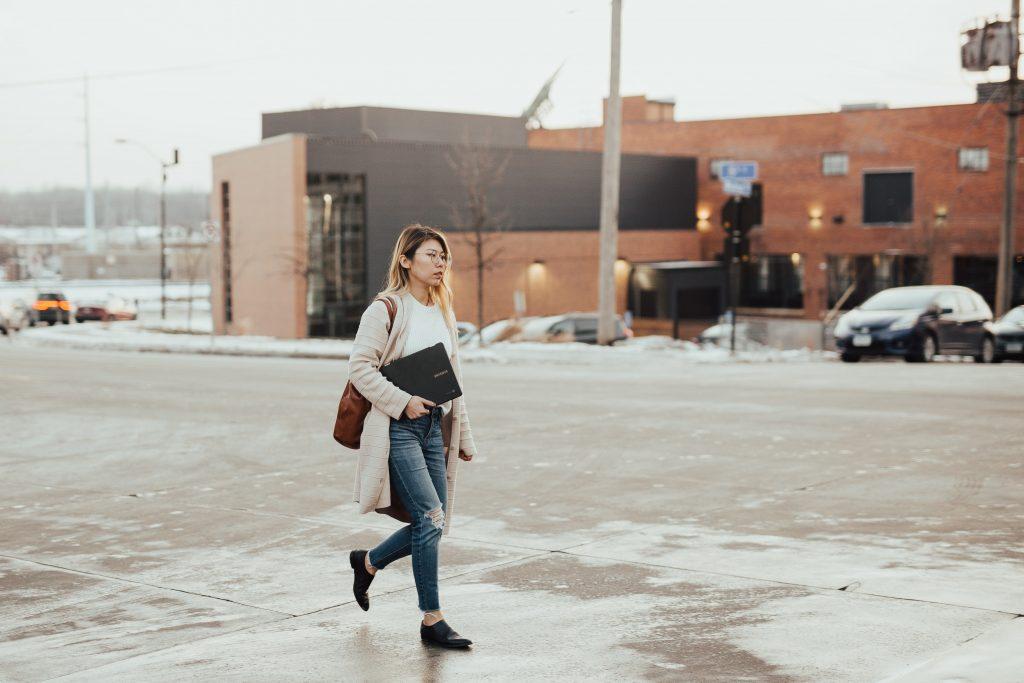 chica caminando con portatil en el brazo