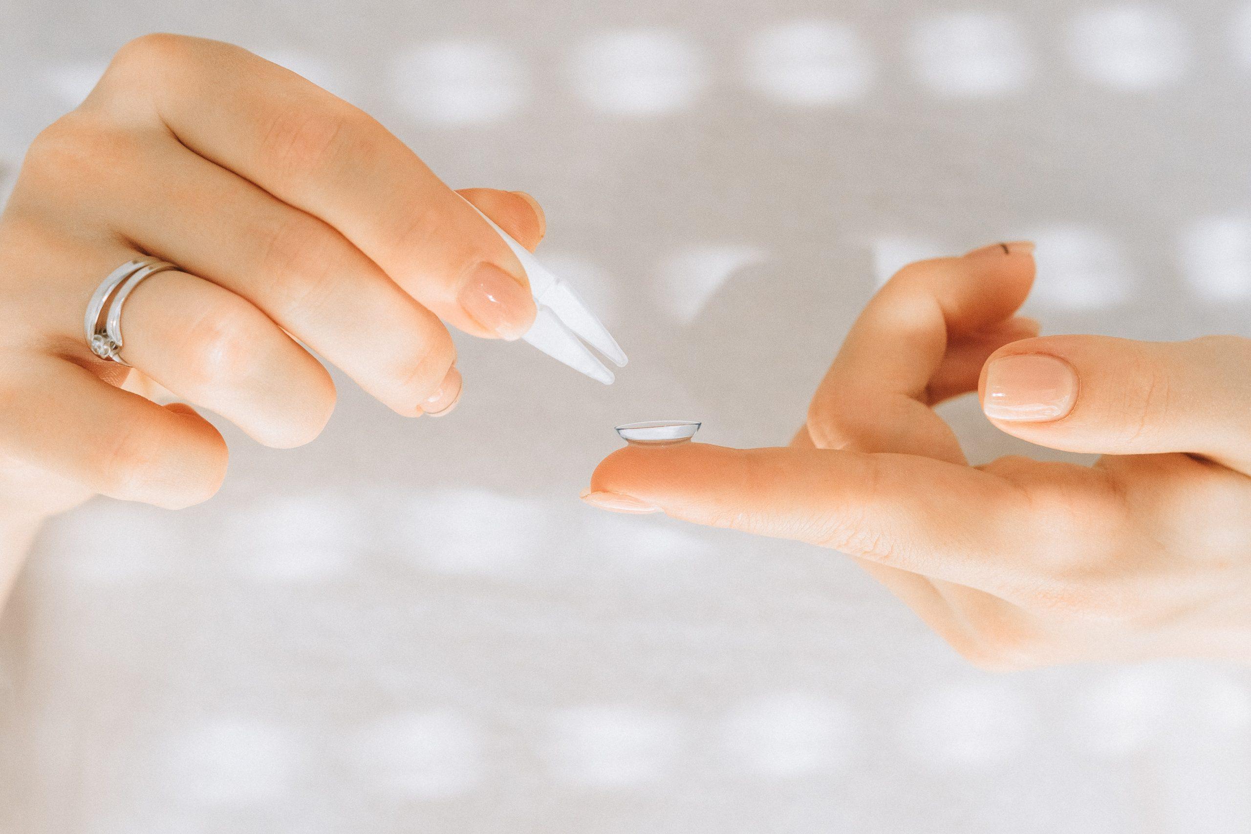Persona tomando lentillas con pinza