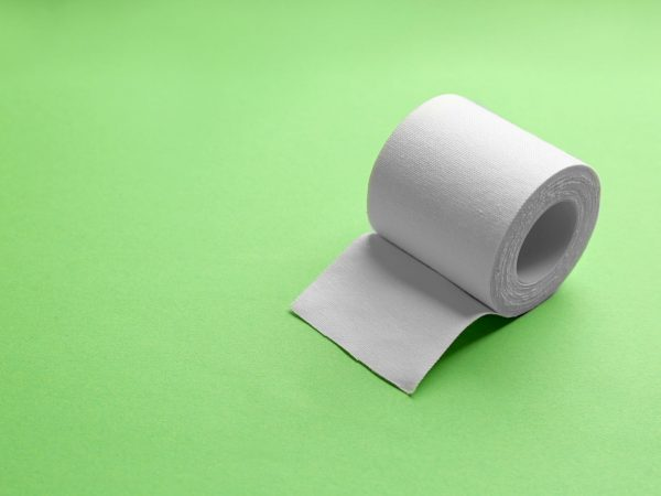 Sticking plaster roll on green background. Space for text