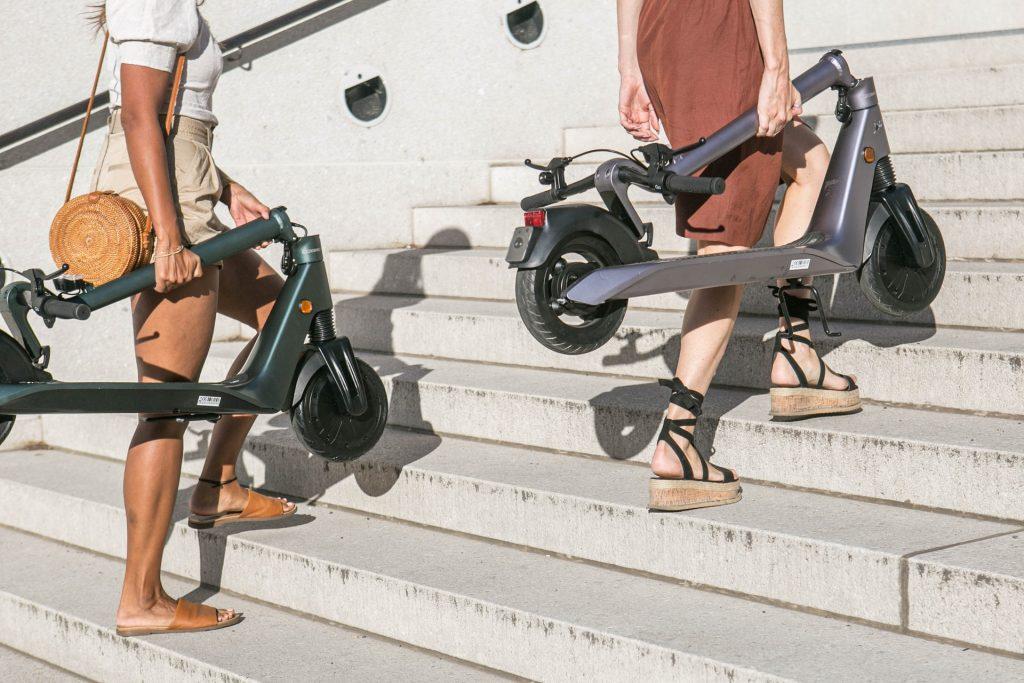 Dos mujeres subiendo escaleras con patinetes electrico
