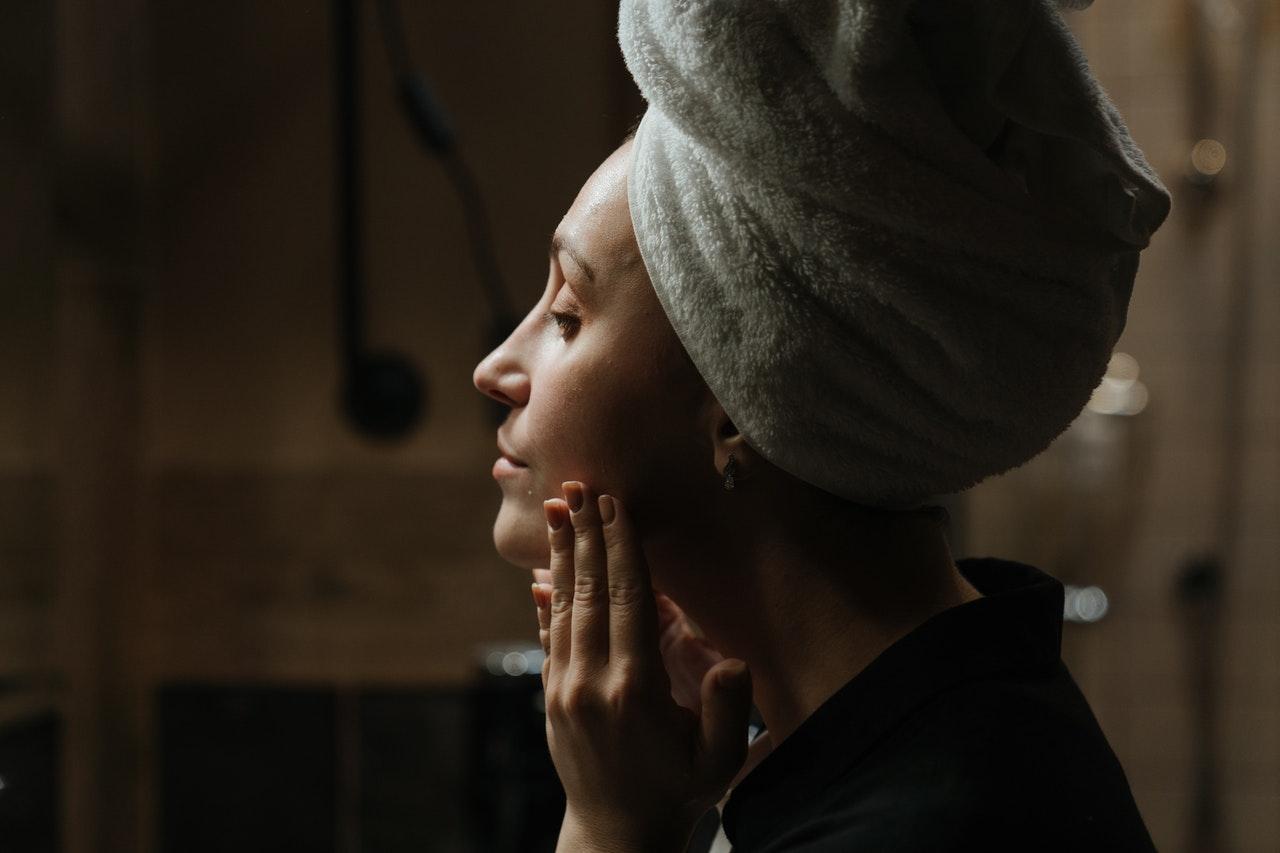 Mujer recien duchada se aplica crema en el rostro