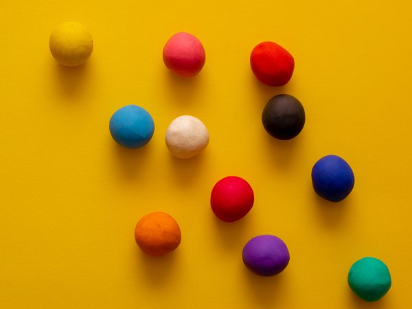 Many different colored plasticine balls on a yellow background. Colorful top down view, hand rolled childrens toys
