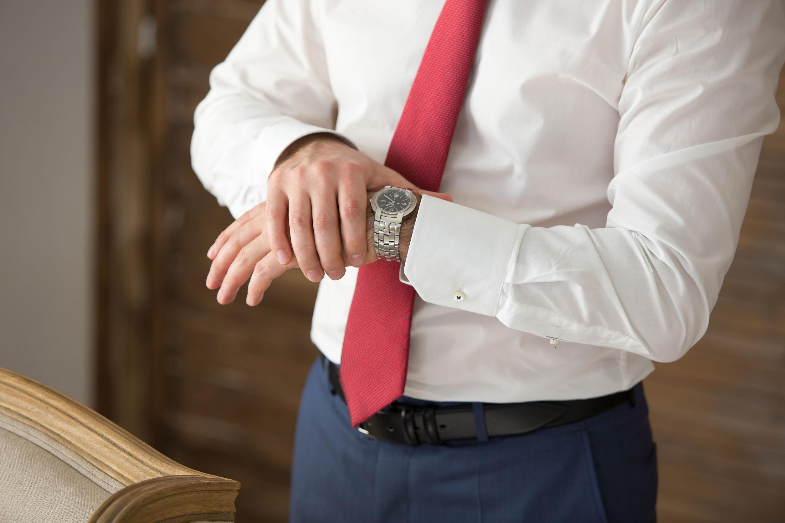 Reloj de los hombres en las manos del hombre en un traje