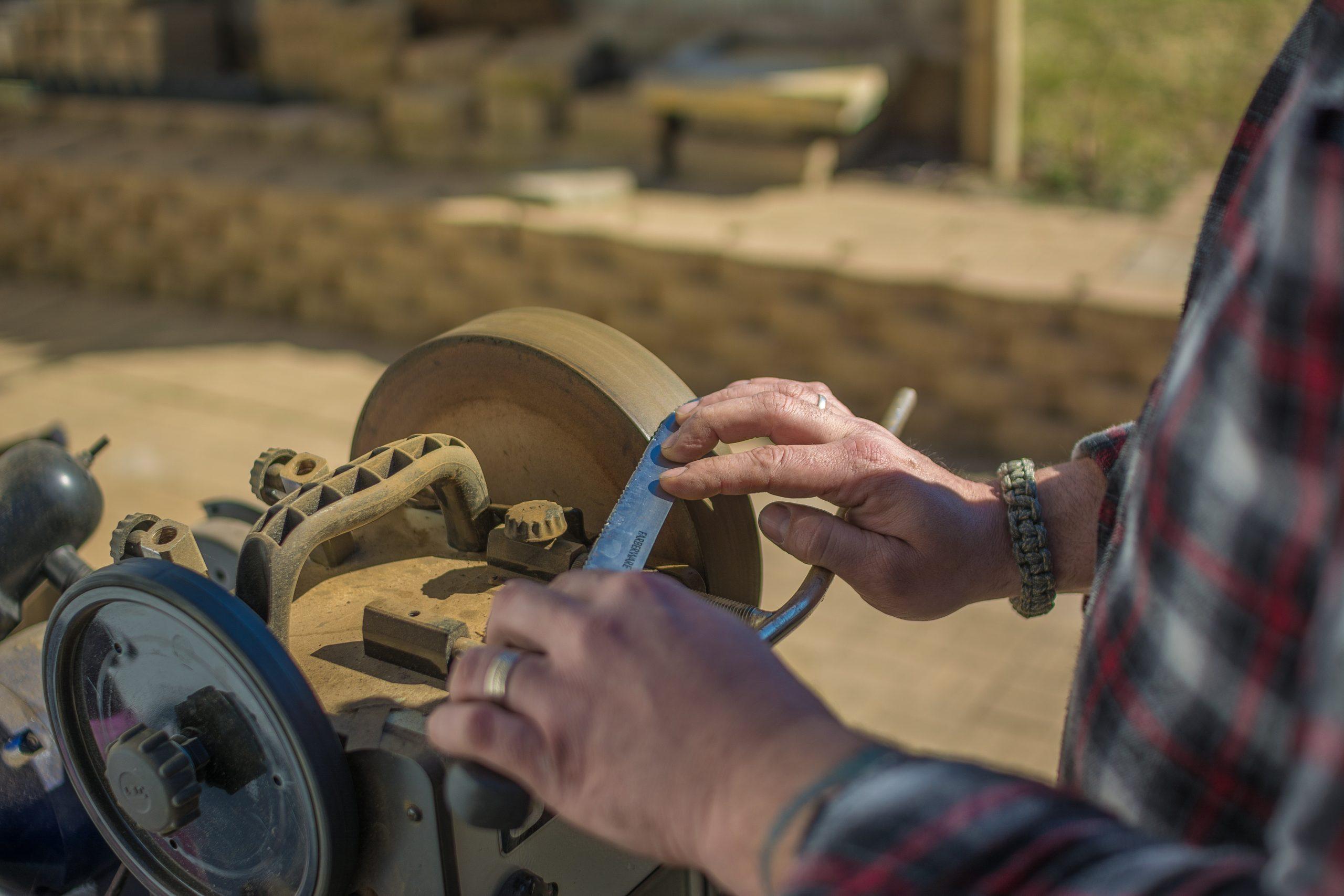 Hombre afilando cuchillo con piedra de afilar
