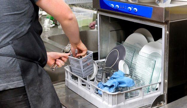 Persona colocando platos en lavavajillas