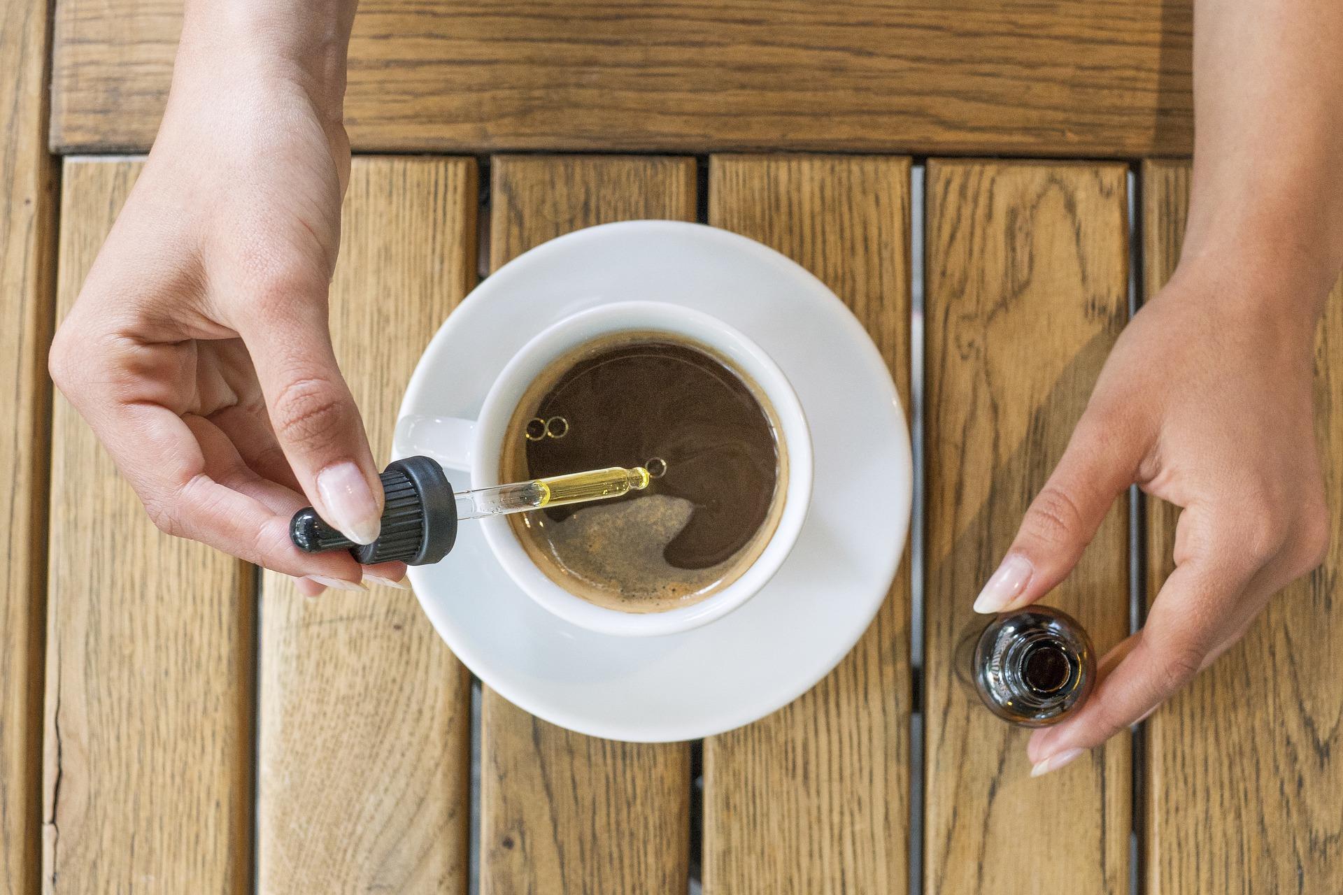 Persona con gotero de aceite de CBD agregando a taza de té