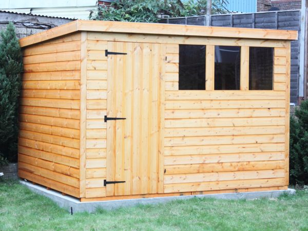 A newly built wooden garden shed sitting on a concrete base
