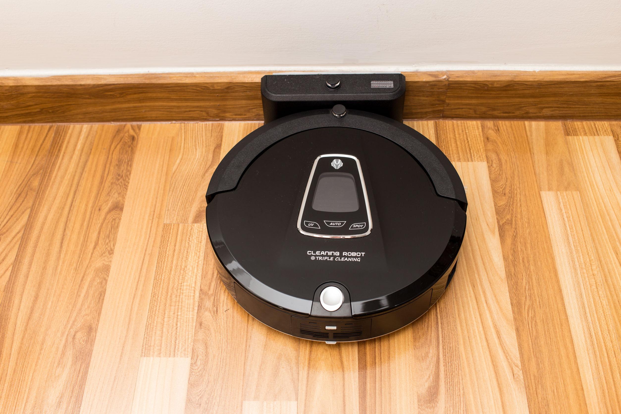 Aspirador robótico en piso de parquet de madera, aspiradora inteligente
